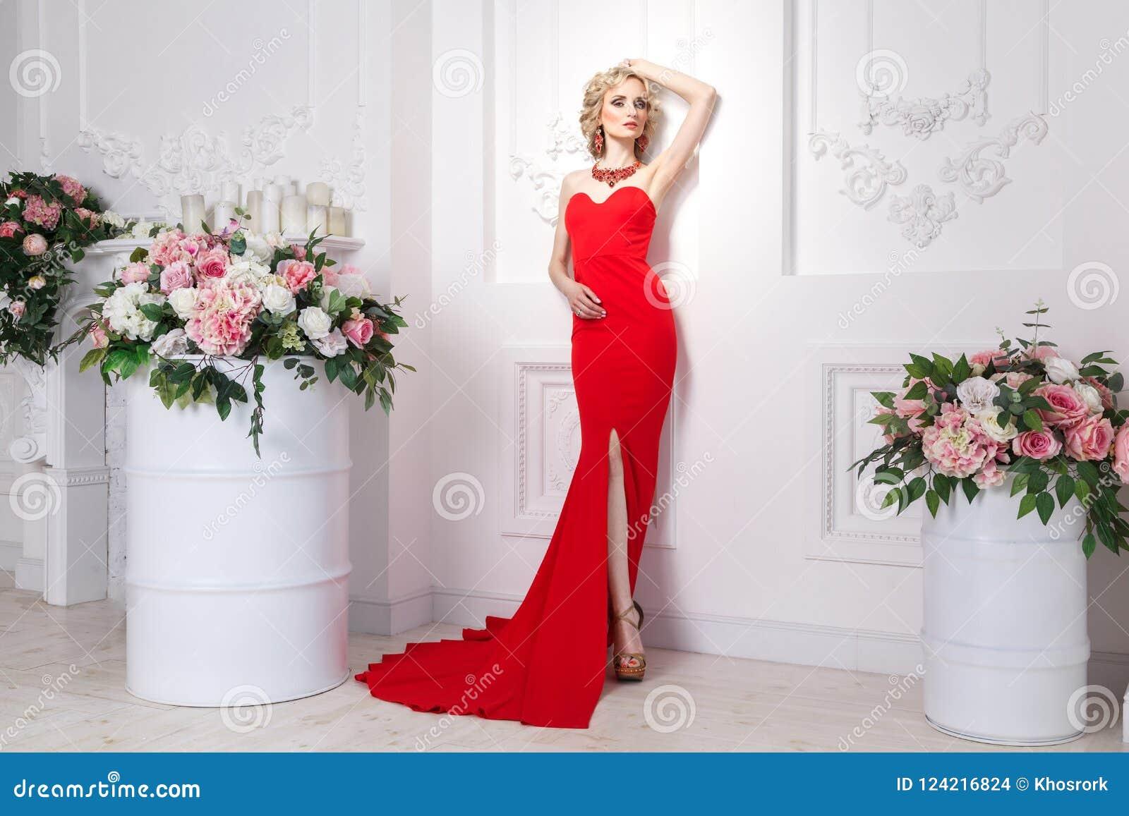 Богато дама с красным длинным платьем, ювелирными изделиями и белокурыми волнистыми волосами, p