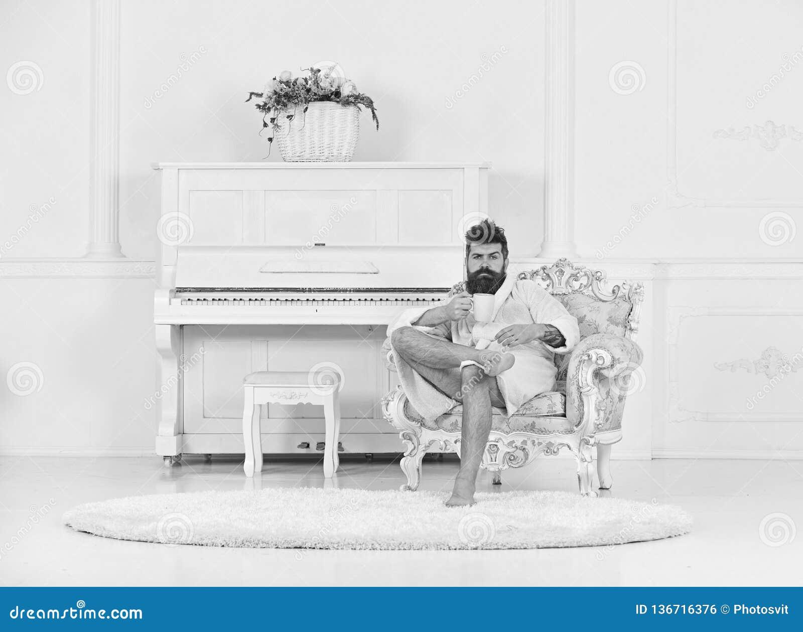 Богатый парень сидя в кресле и выпивая чае или кофе Бородатый парень в белой комнате Совершенная концепция утра
