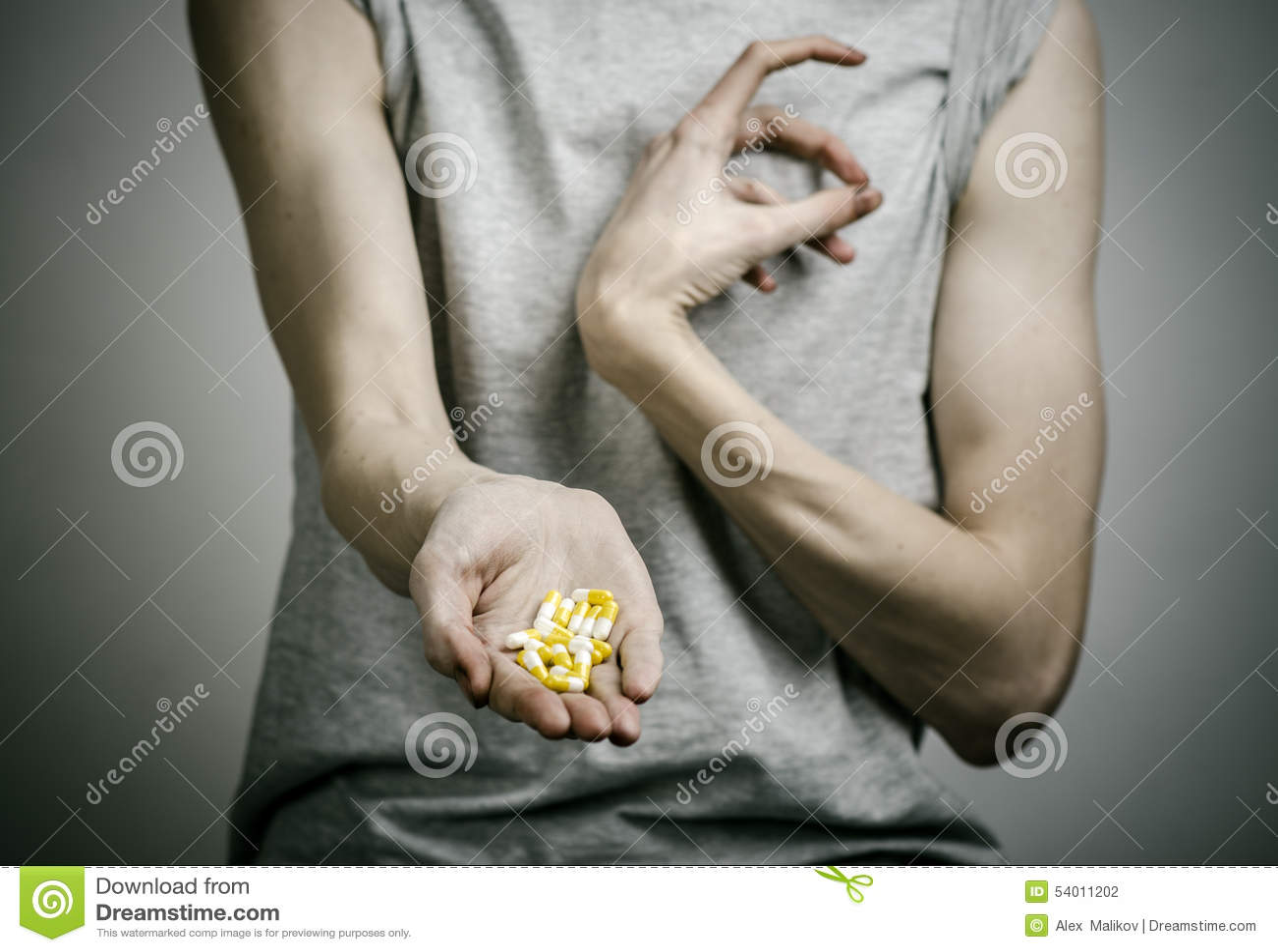 Бой против лекарств и темы наркомании: addict держать наркотические пилюльки на темной предпосылке
