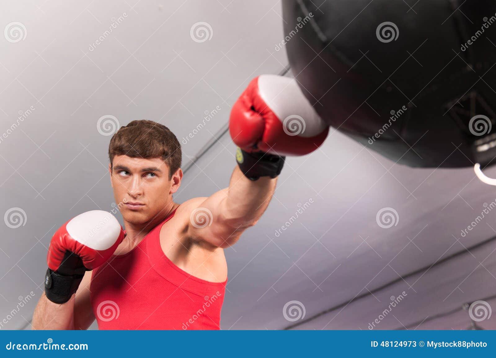 Боксер делая некоторую тренировку на груше на спортзале
