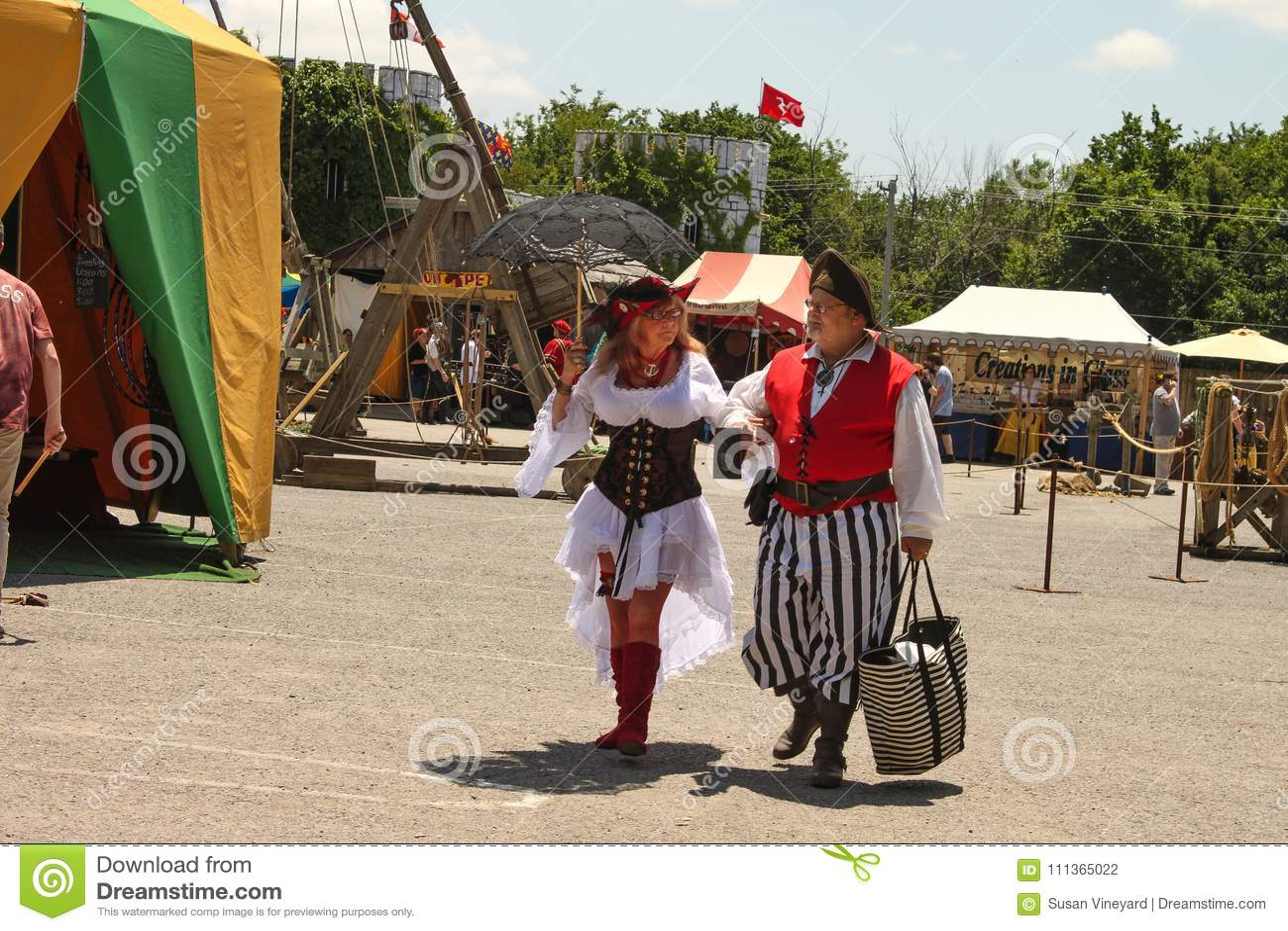 Более старая женщина одела в очень сексуальном костюме и более старом человеке одетых как взгляд пирата на одине другого любяще п