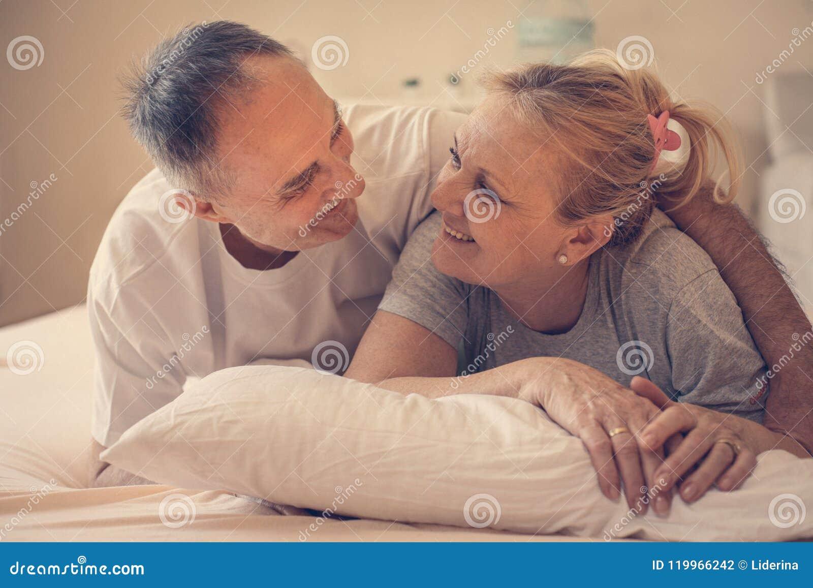 русская пожилая пара лежат в кровати им, ракам