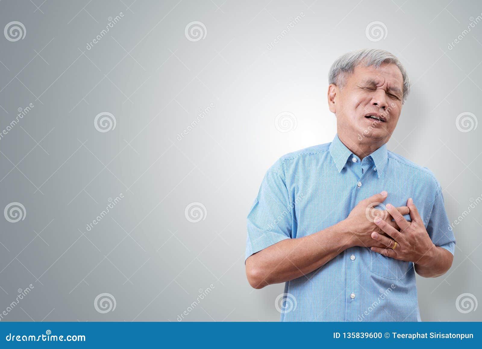 Более старый азиатский человек схватывая и имея причину боли в груди от сердечного приступа Сердечная болезнь в старшем человеке
