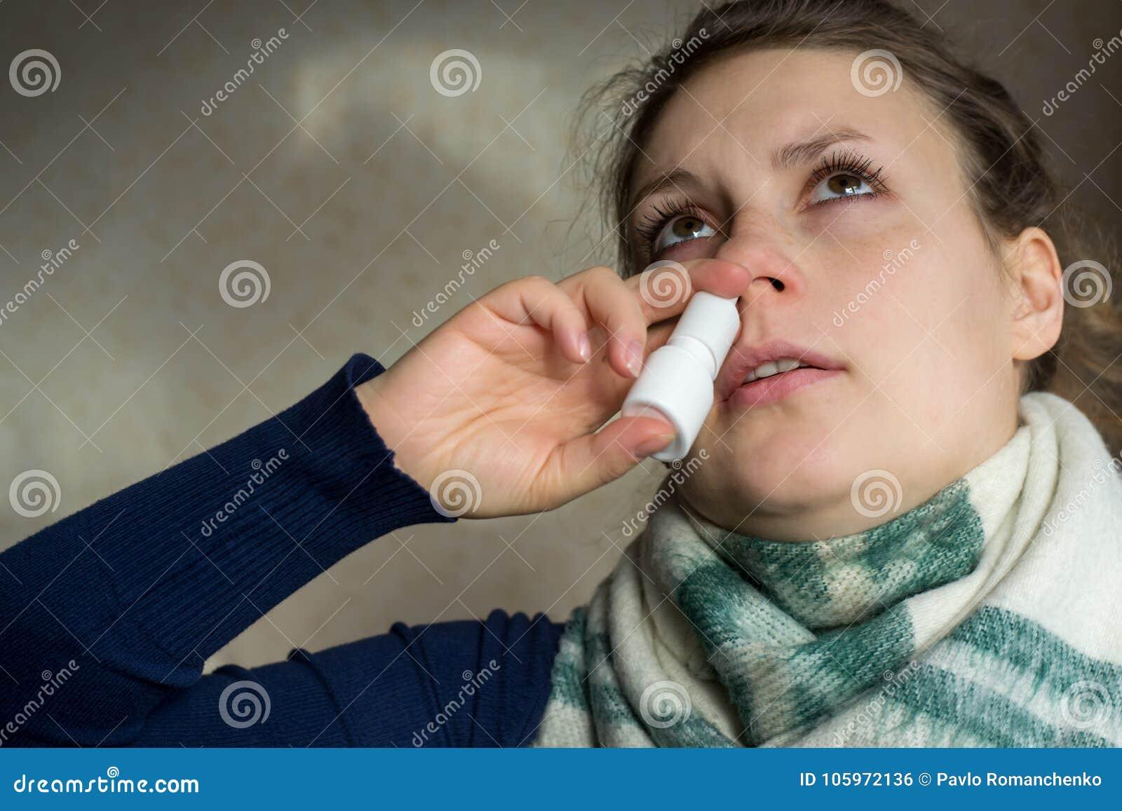 Больная девушка распыляет брызг от жидкого носа в носовой пропуск
