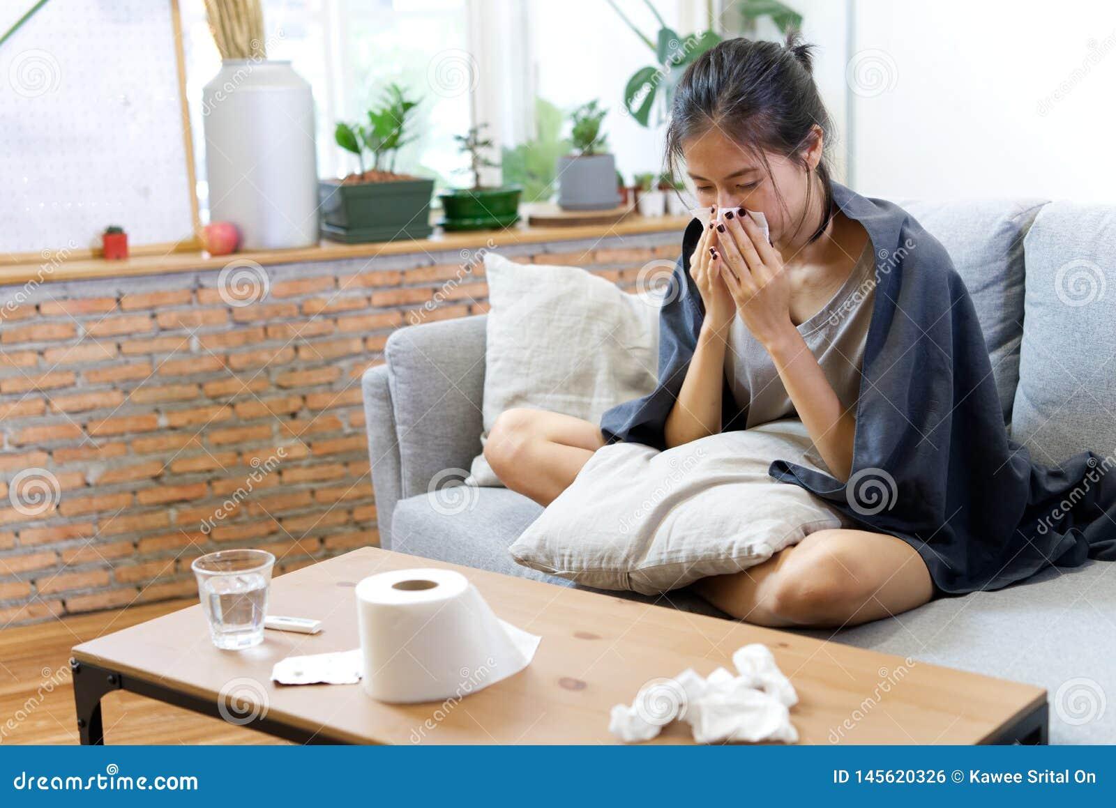 Больное азиатское чихание молодой женщины дома на софе с холодом
