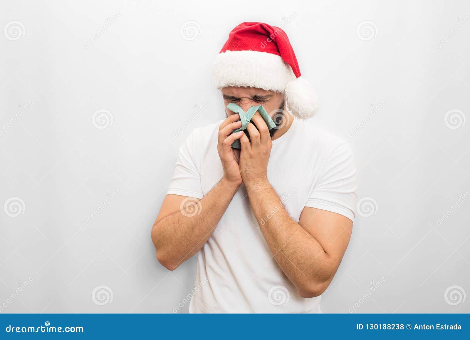 Больной молодой человек в красных стойках и чиханиях шляпы в салфетке Он ILL Гай в несчастном белизна изолированная предпосылкой