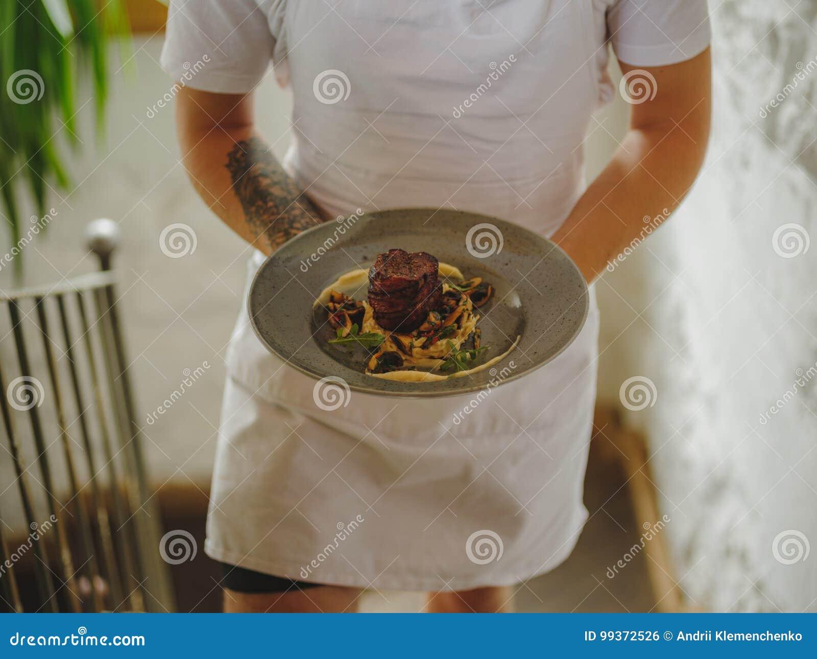 Большая голубая плита с очень вкусным блюдом в мужских руках на запачканной предпосылке лестниц Кельнер с заказом скопируйте косм