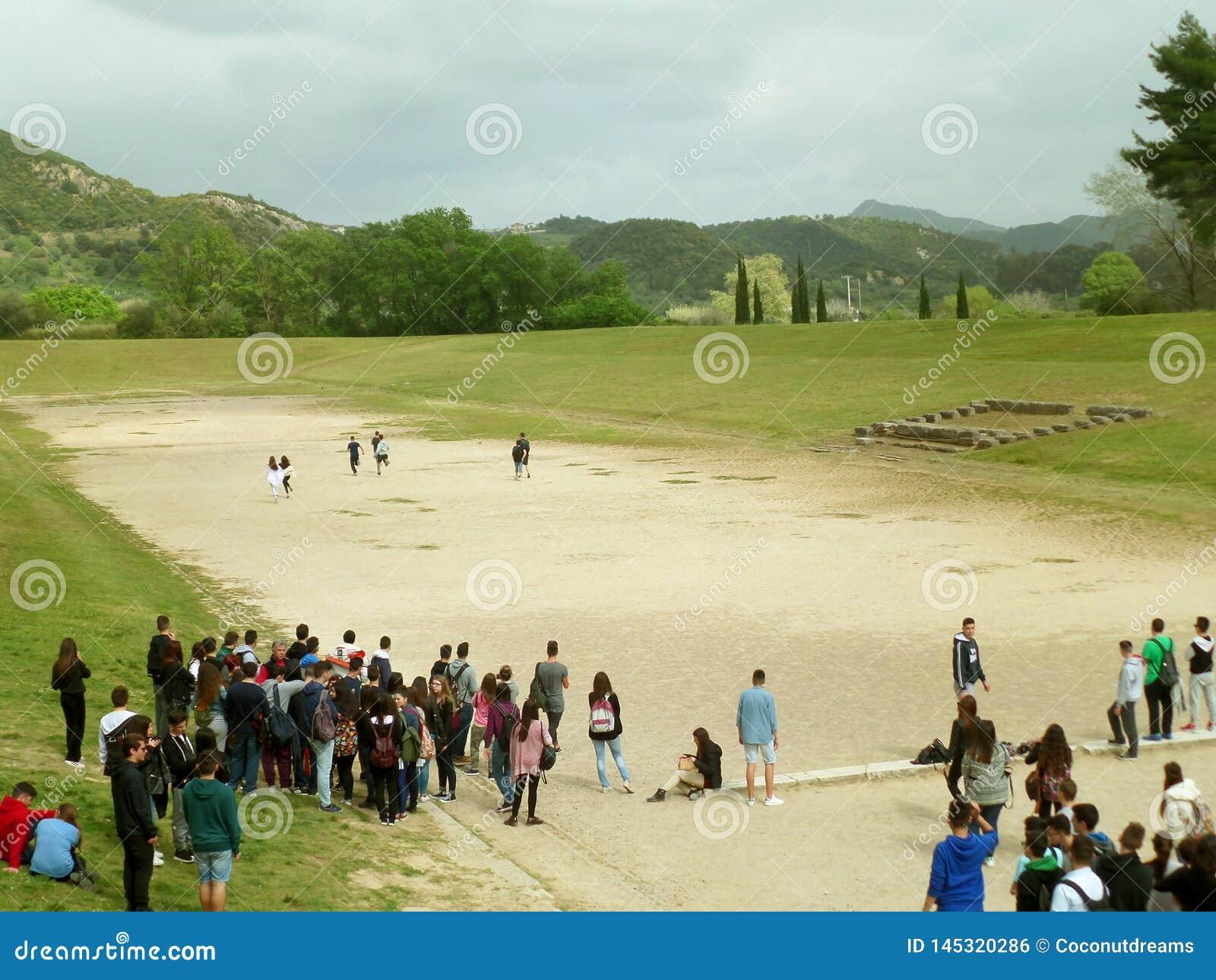 Большая группа в составе студенты наслаждается посетить старый стадион старой Олимпии, места всемирного наследия ЮНЕСКО в Греции