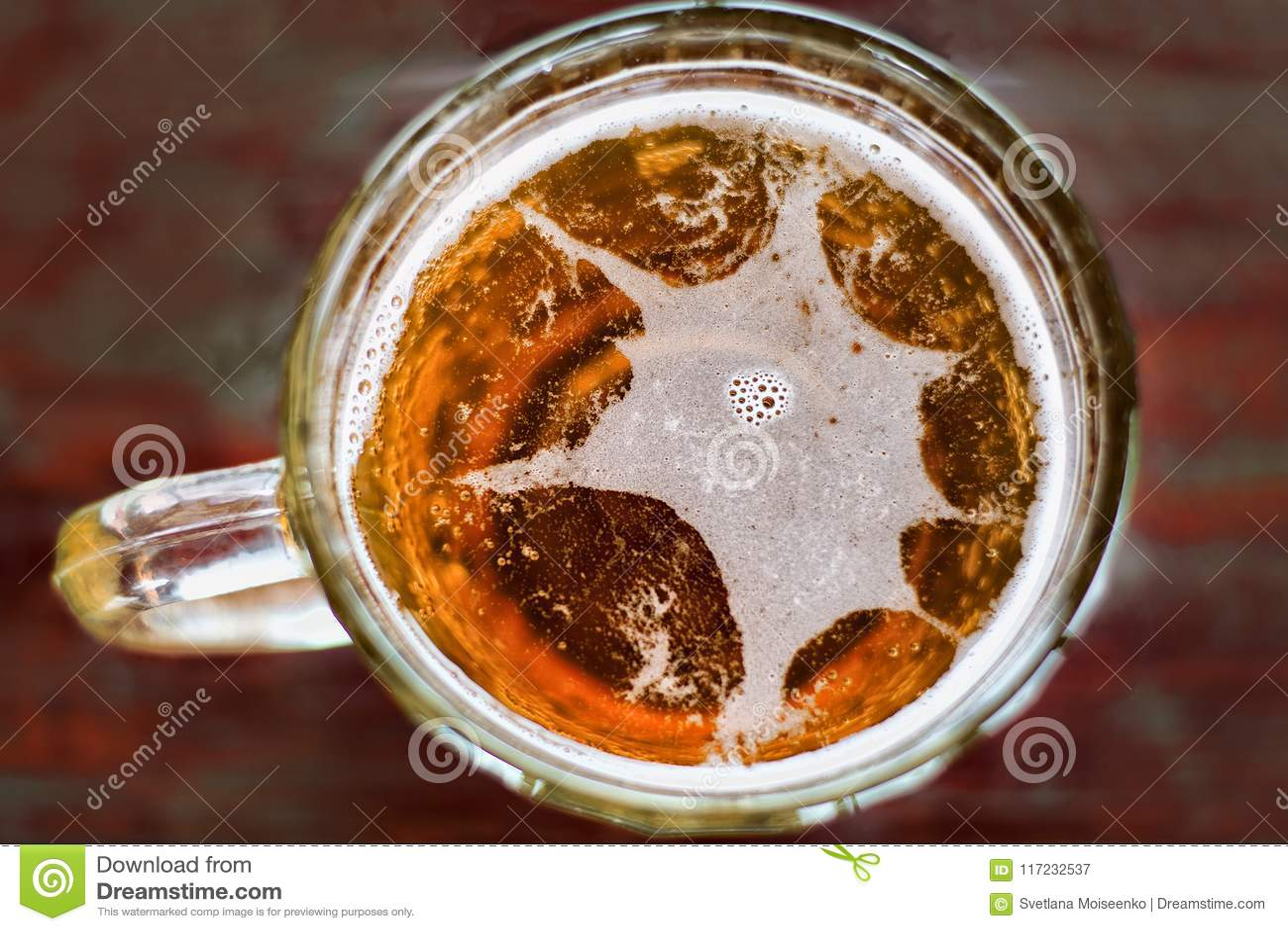 Большая кружка пива с взгляд сверху пены и пузырей с солнцем