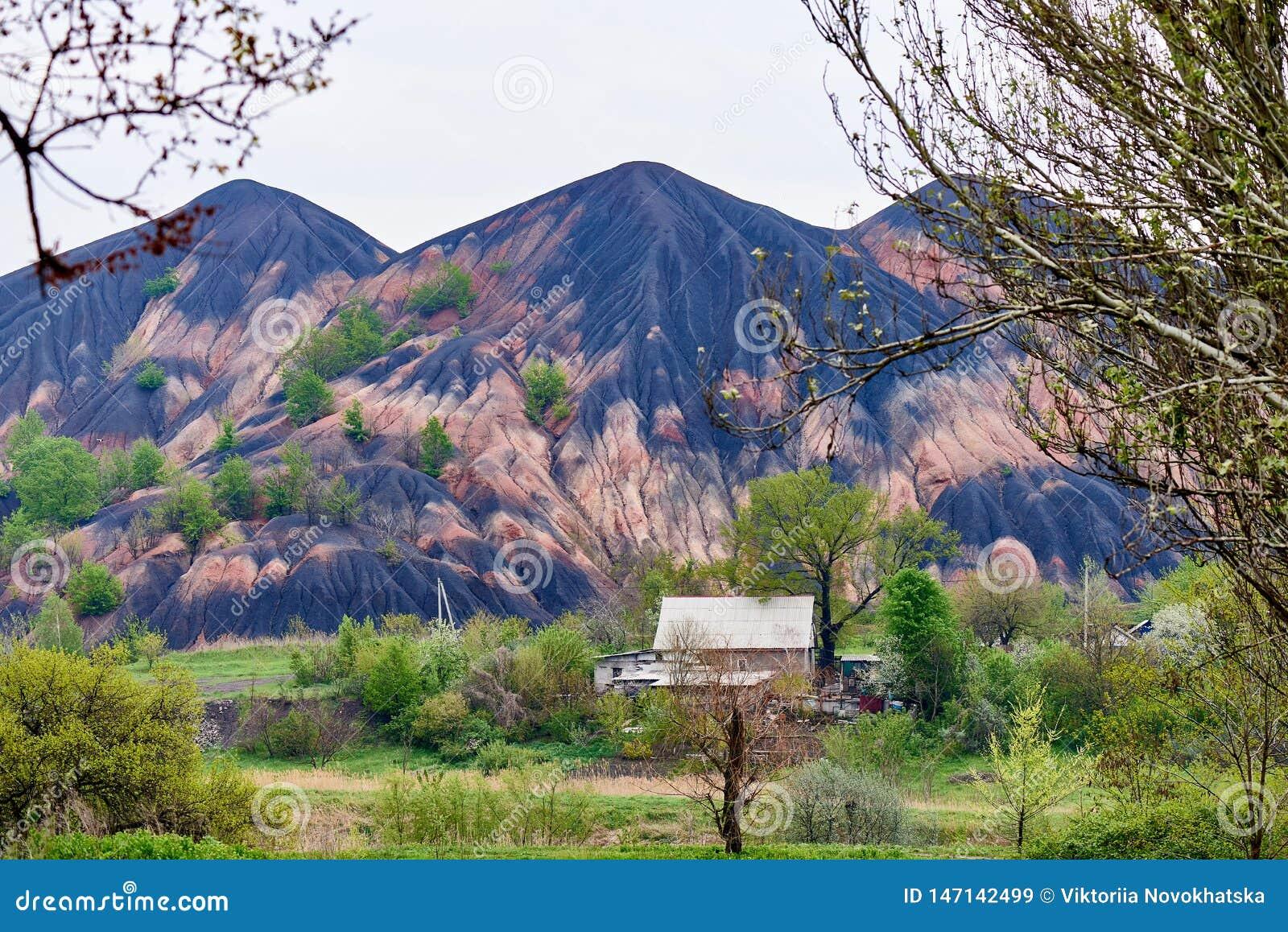 Большая куча шлака и небольшая деревня среди цветя деревьев весны