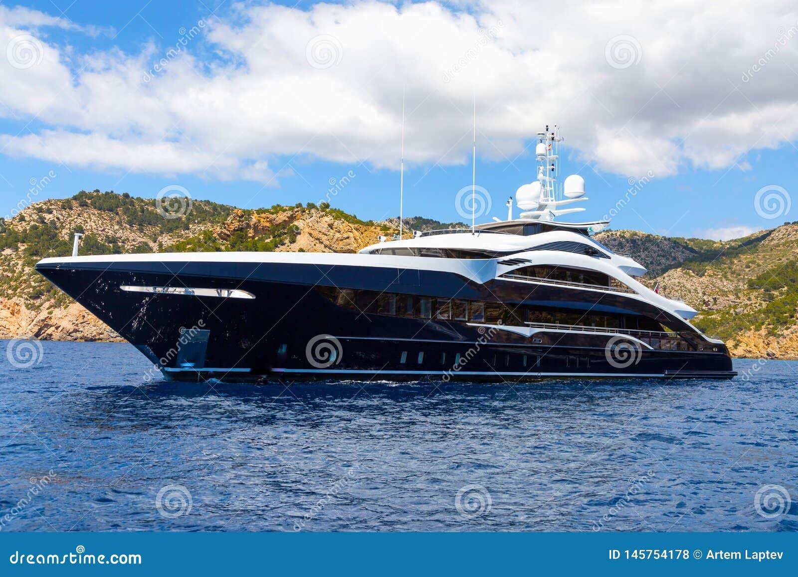 Большая роскошная яхта мотора против фона гор