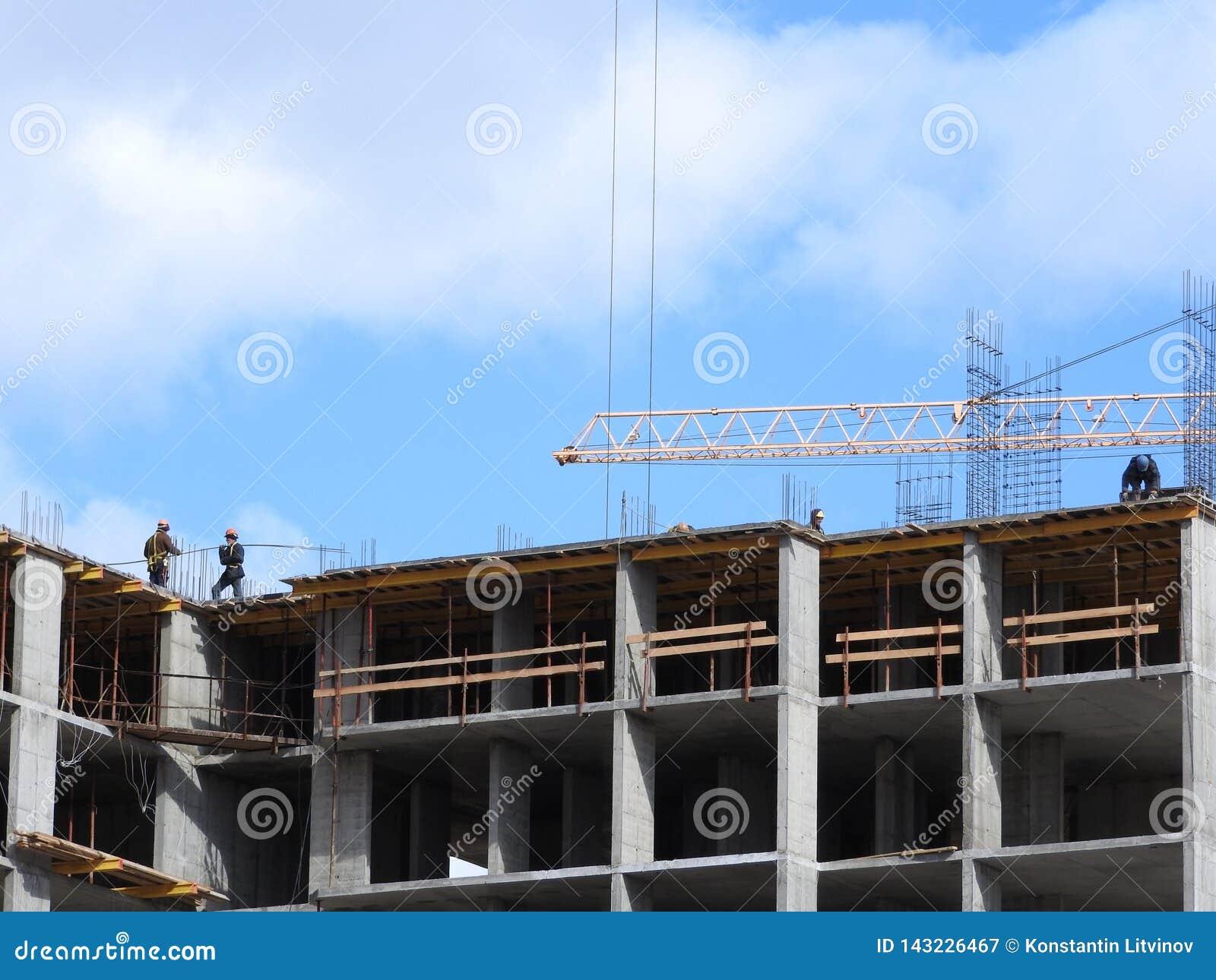 Большая строительная площадка, включая несколько кранов работая на комплексе конструкции, с ясным голубым небом