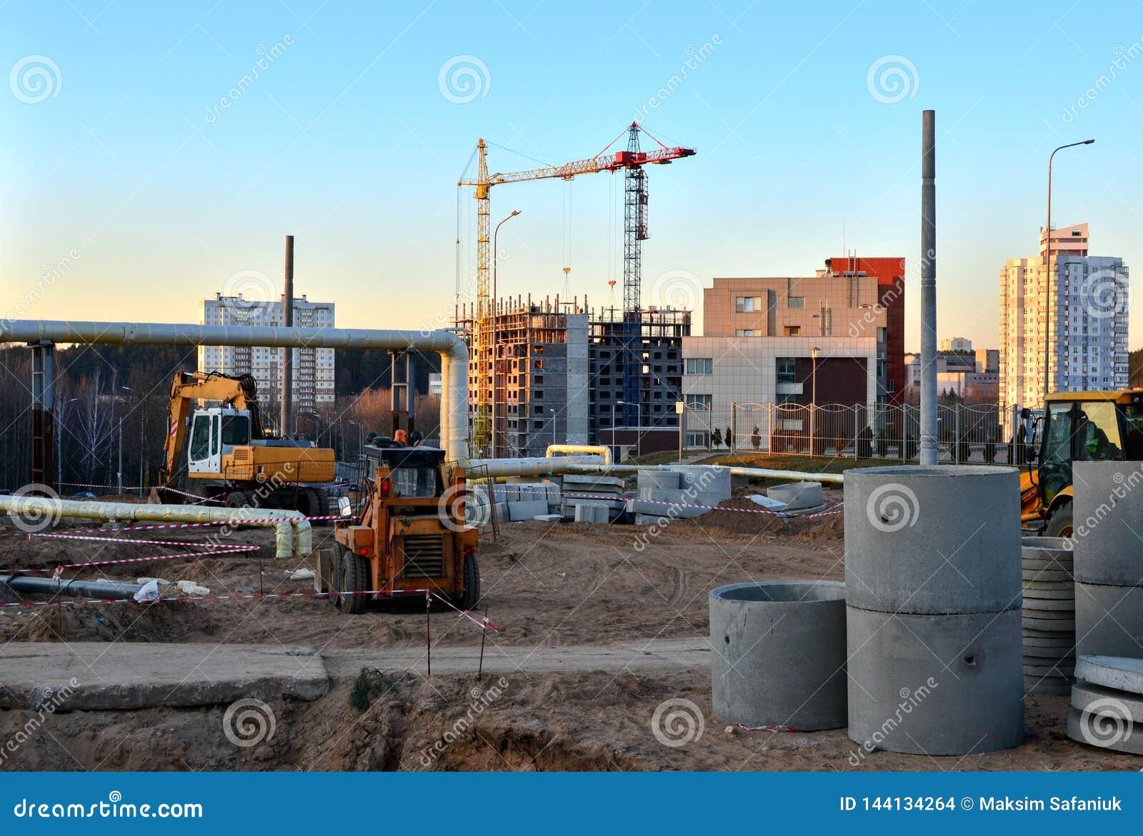 Большая строительная площадка с работая кранами и тяжелой техникой для дорожных работ, затяжелителем колеса, бульдозером, экскава