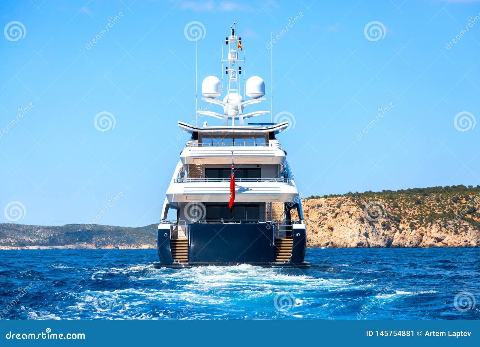Большая частная яхта мотора в процессе вне на море, взгляд задней части