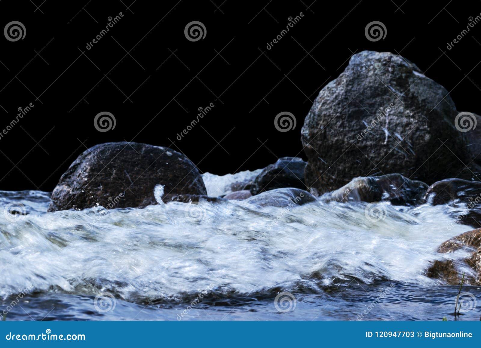 Большие ветреные волны брызгая над утесами Развевайте выплеск в озере изолированном на черной предпосылке Волны ломая на каменист