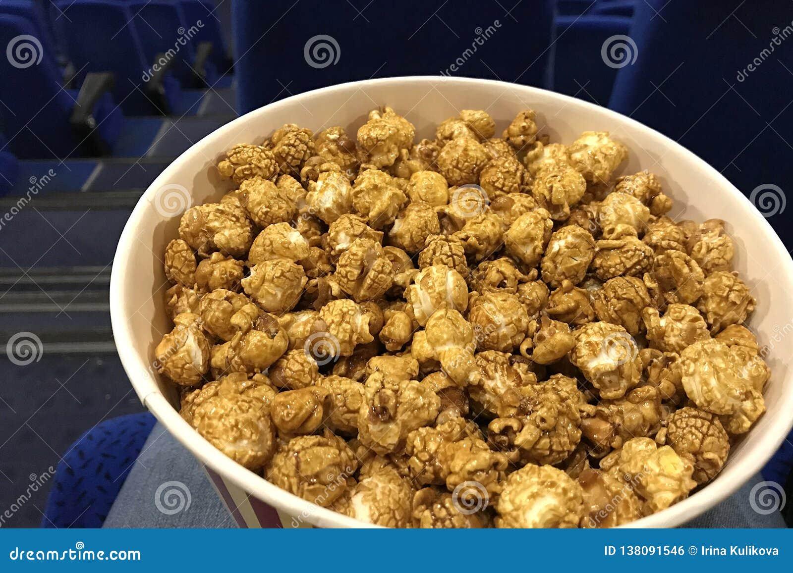 Большое ведро очень вкусного попкорна карамельки на подоле человека ждать фильм для начала на кино