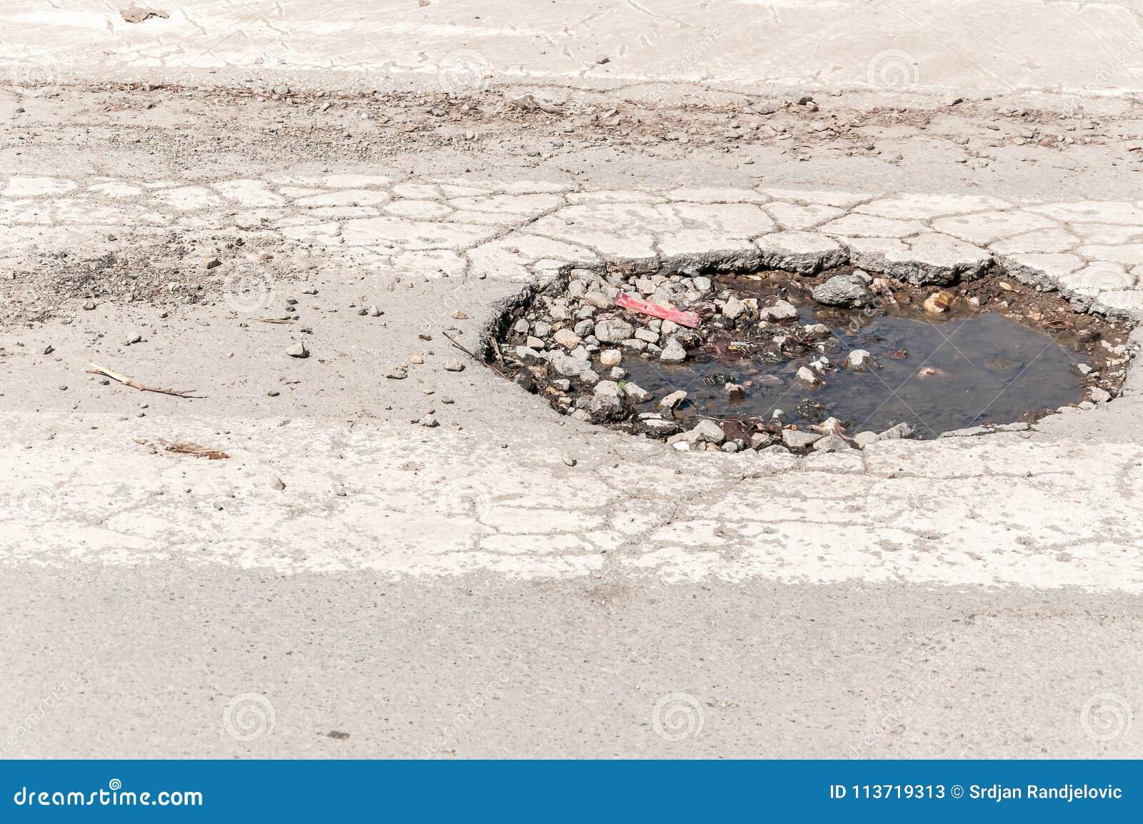 Большое глубокое опасное отверстие в дороге асфальта, опасность для управлять автомобилей может причинить аварию или нервное расс