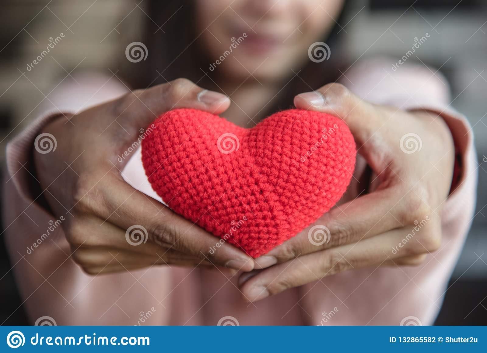 Большое красное сердце пряжи держа и давая для того чтобы противостоять рукой женщины Lo
