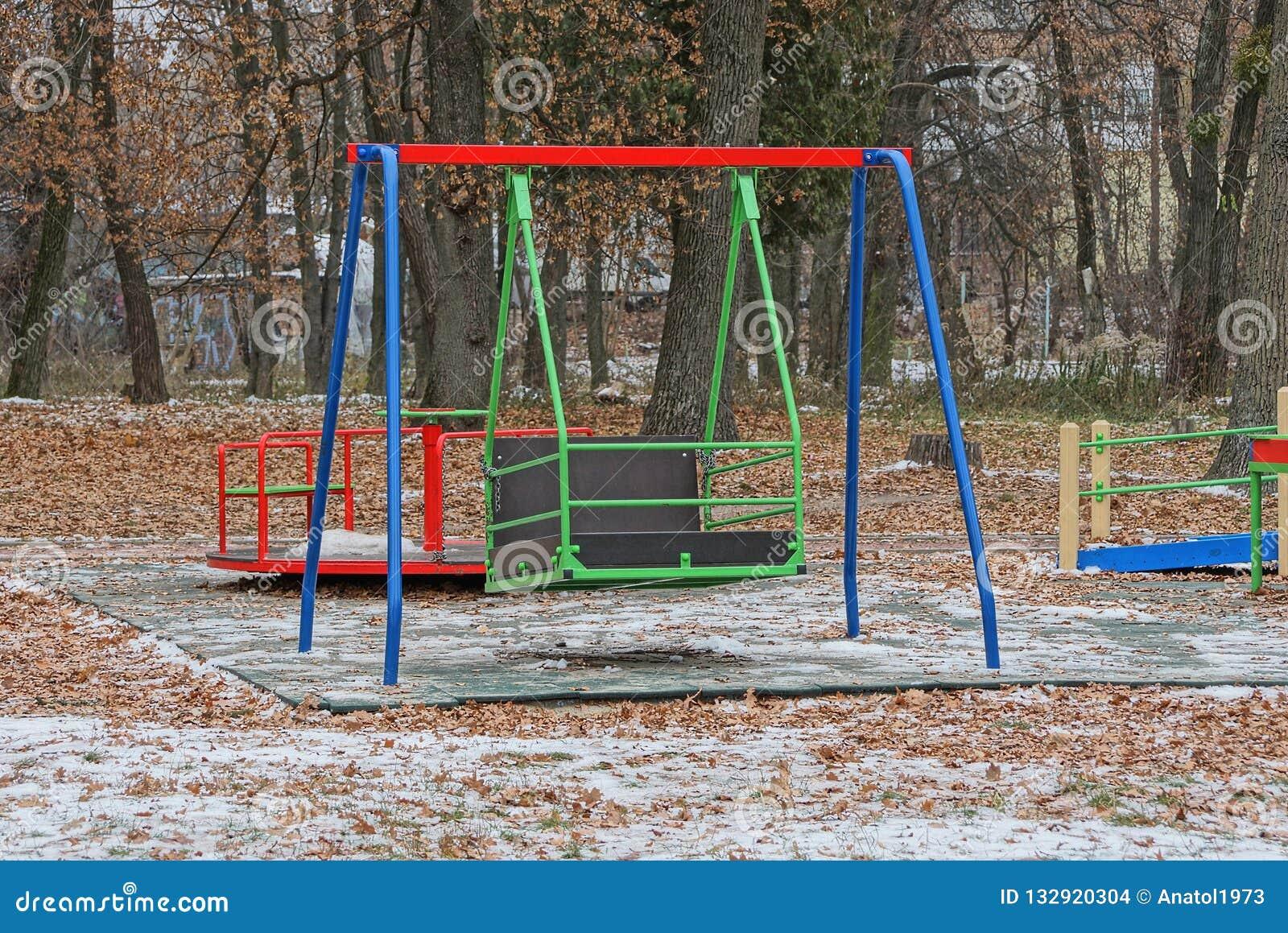 Большое покрашенное качание утюга на спортивной площадке в парке зимы