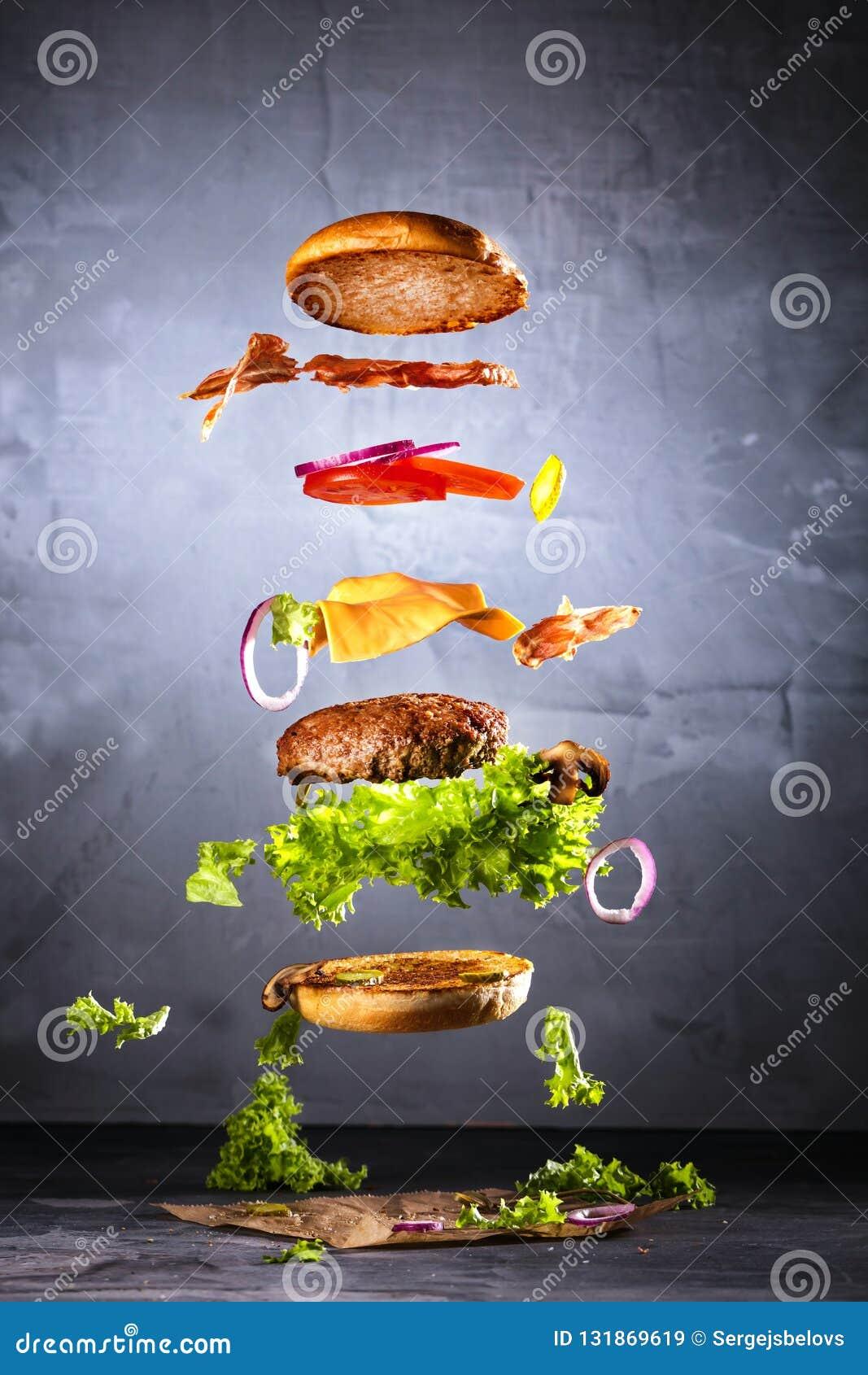 Большой вкусный домашний сделанный бургер с ингридиентами летания