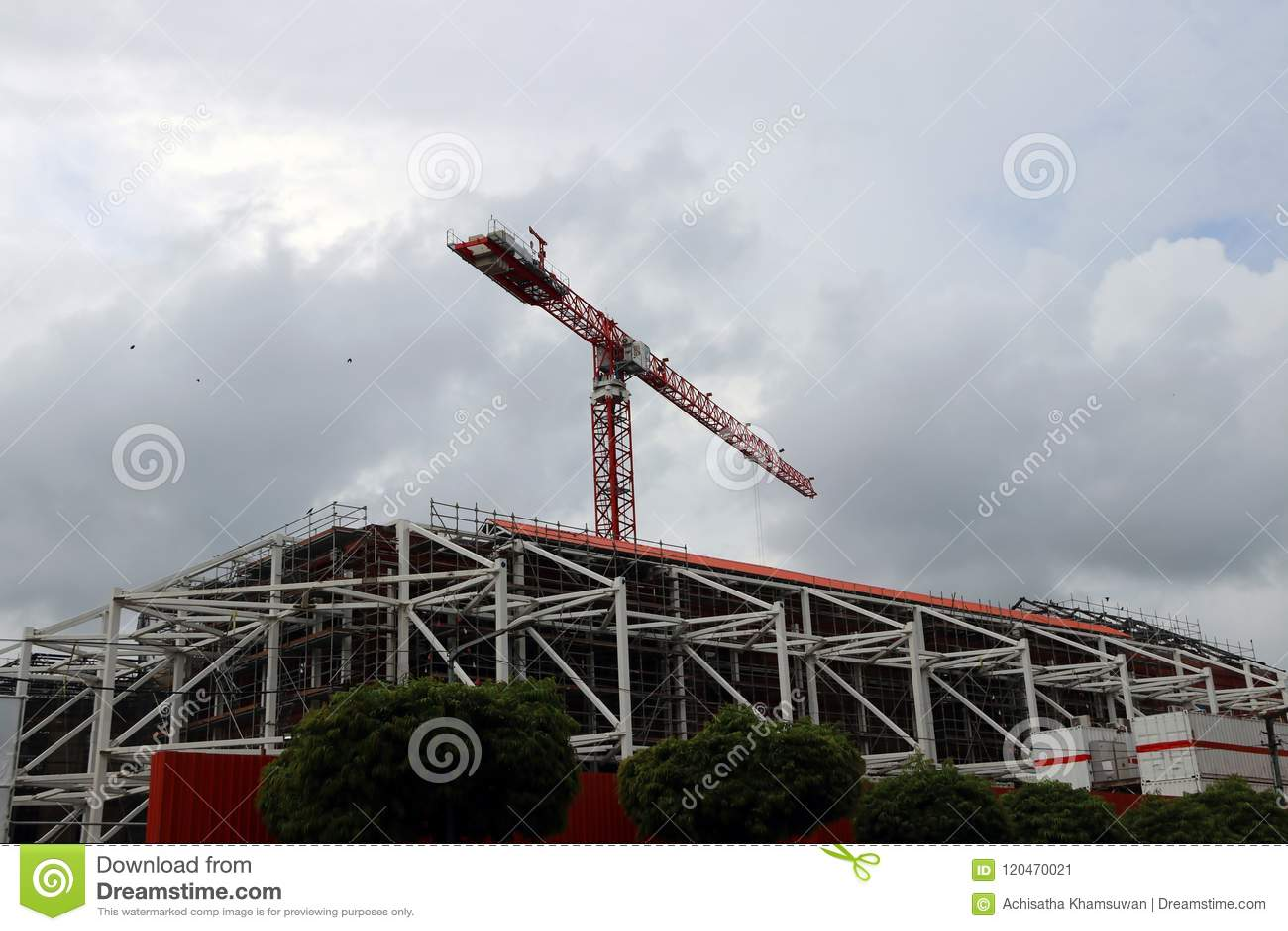 Большой кран над конструкцией здания на предпосылке облака и неба