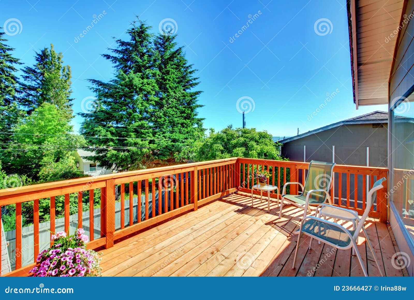 Большой новый деревянный экстерьер дома палубы с стулами.