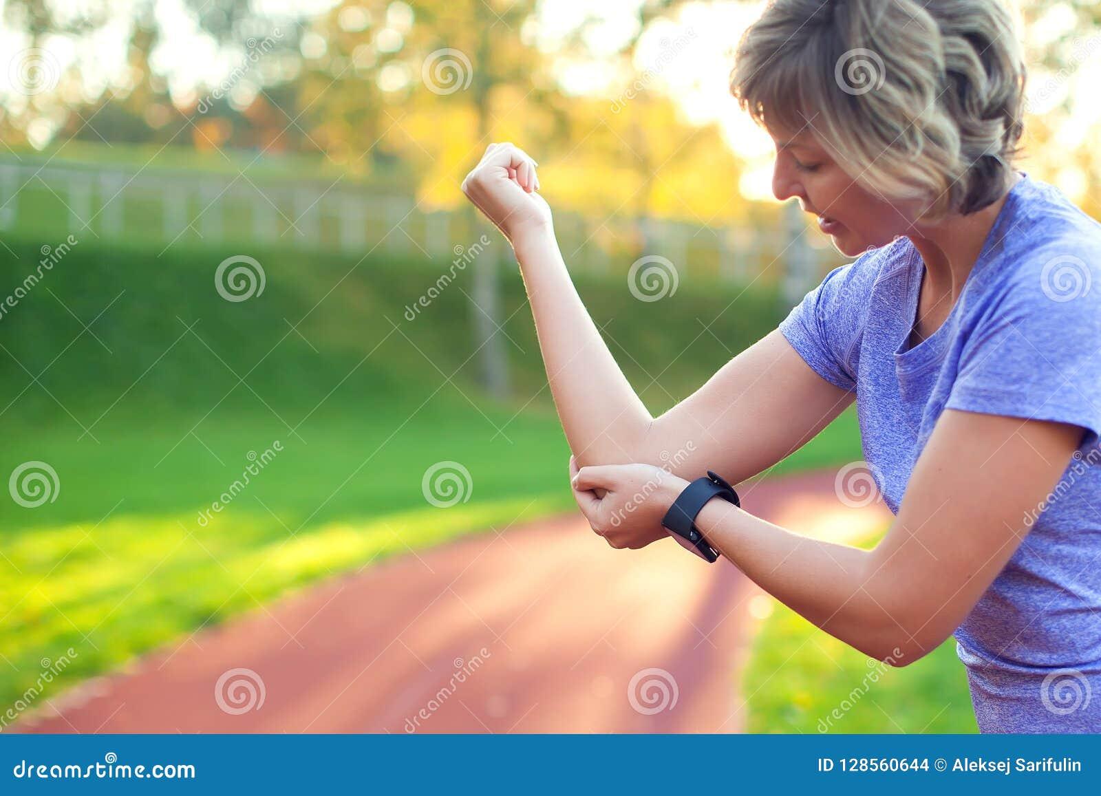 Боль чувства молодой женщины в ее локте во время разминки спорта на st