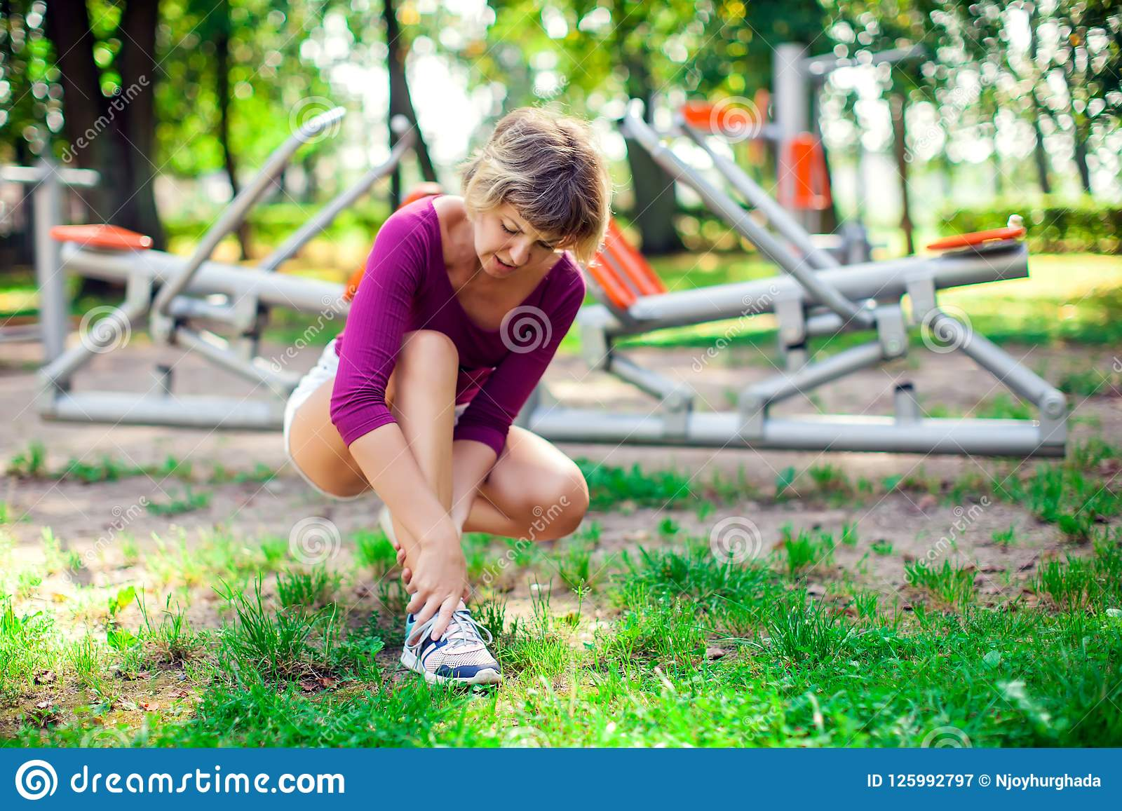 Боль чувства молодой женщины в ее ноге во время разминки спорта в