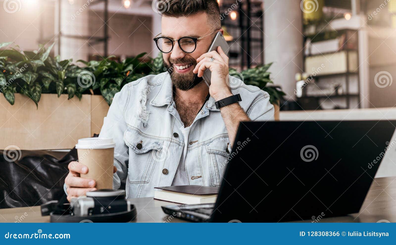 Бородатый бизнесмен, блоггер сидя в кафе, говорящ на умном телефоне, работая на компьтер-книжке, фрилансер работая в кофейне