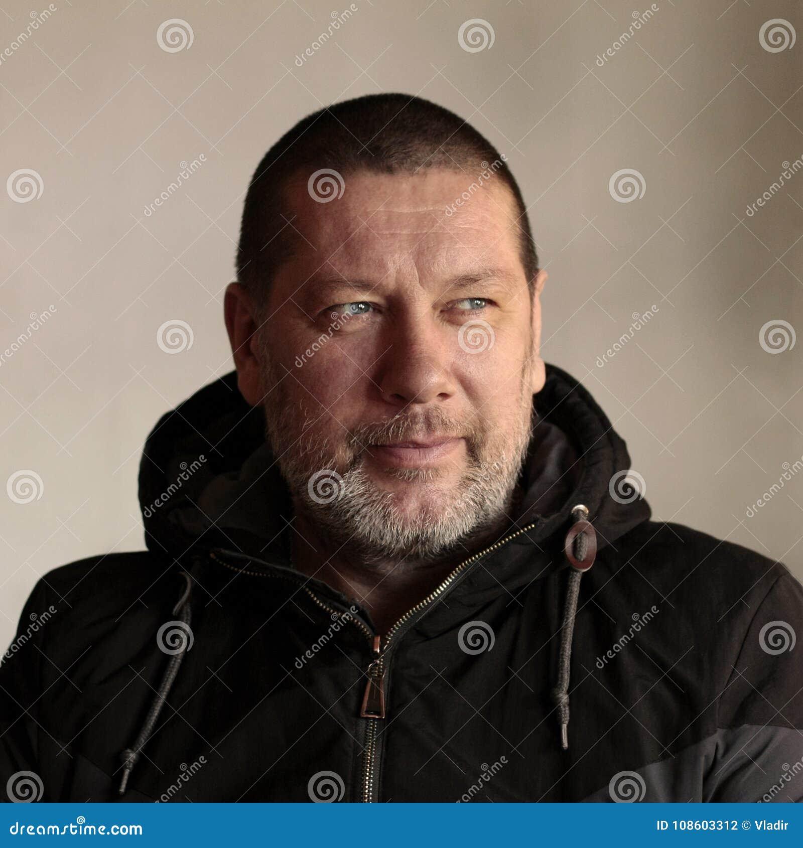 Бородатый 40-год-старый человек смотрит к левой стороне