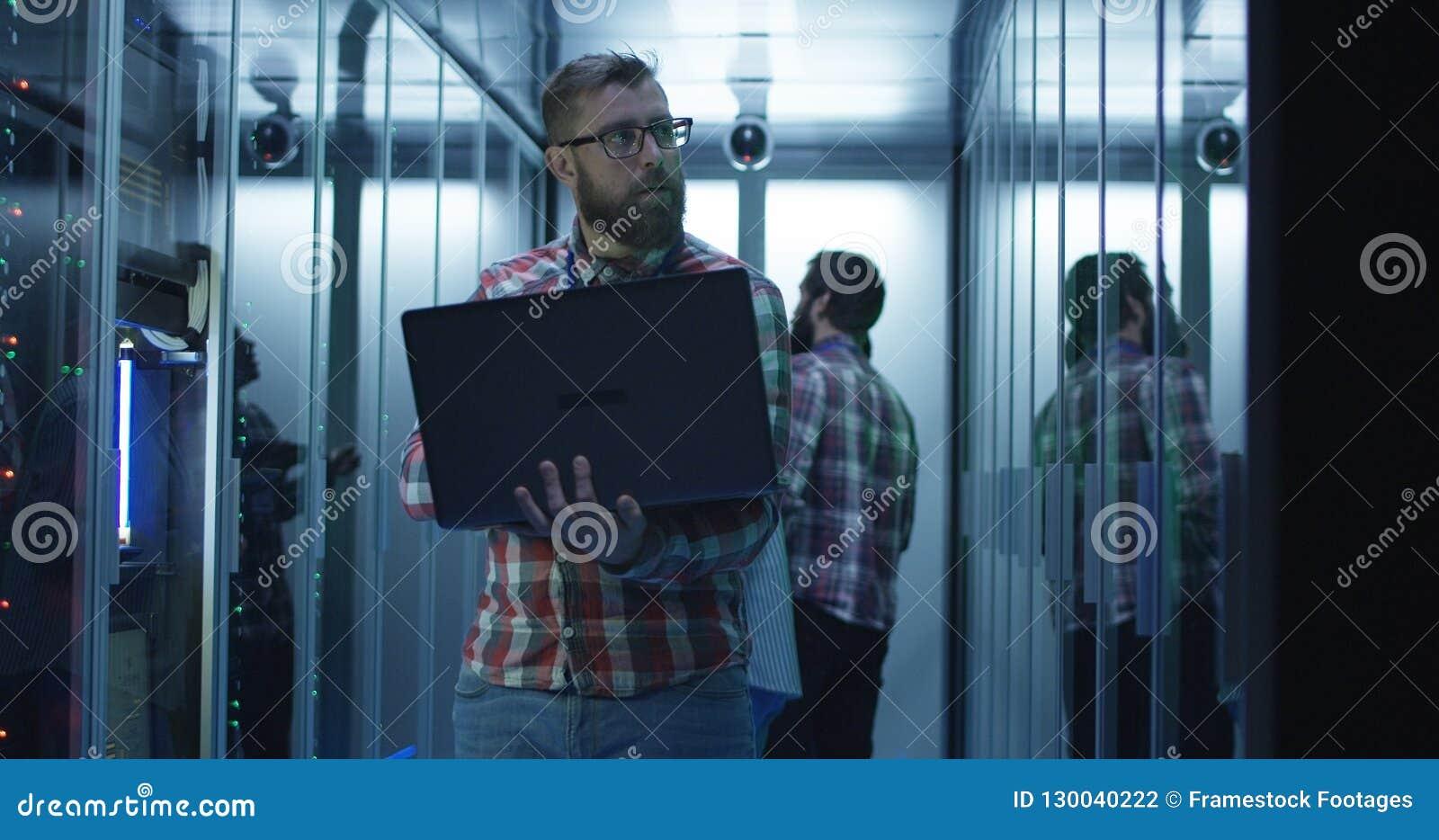 Бородатый инженер ИТ используя ноутбук в комнате сервера
