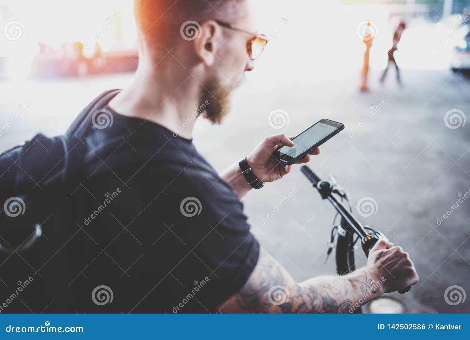 Бородатый мышечный татуированный хипстер в солнечных очках используя смартфон после ехать электрическим скутером в городе