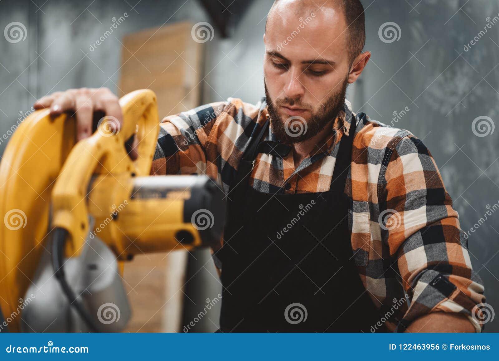 Бородатый работник используя электрический угловой шлифовальный станок в мастерской Обслуживать машин
