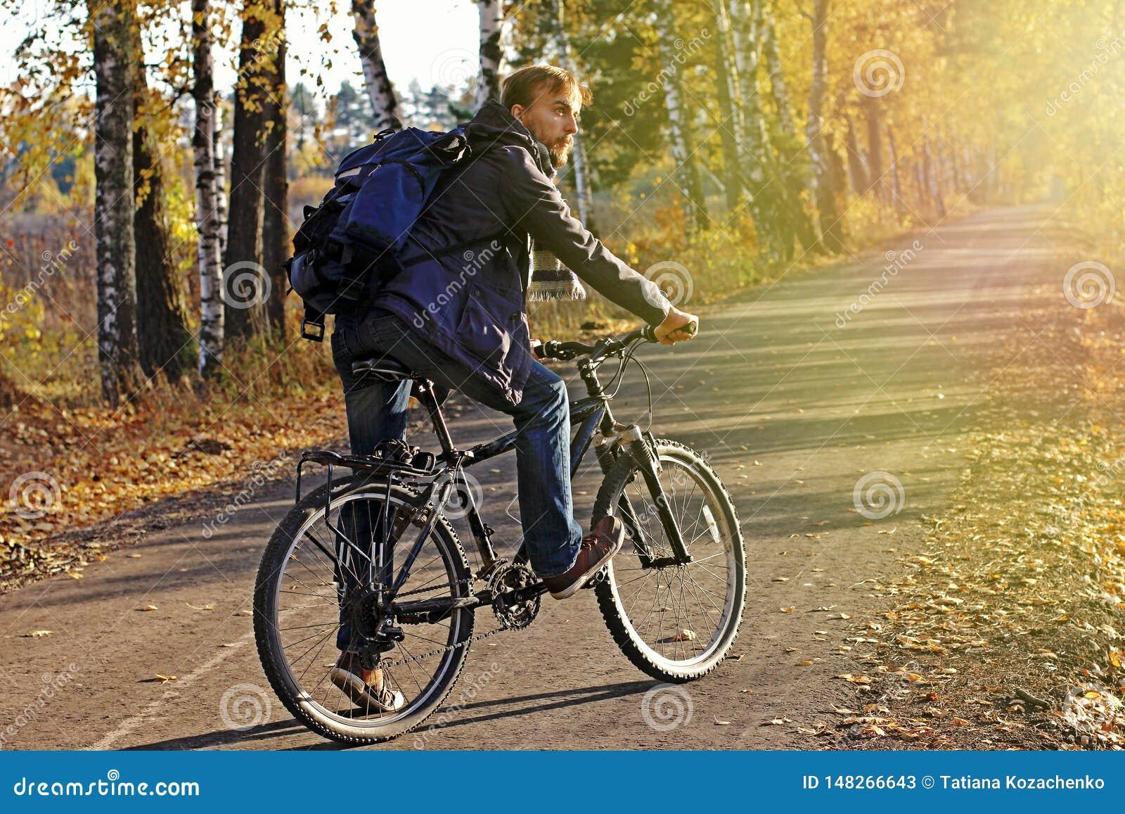 Бородатый человек хипстера в случайной носке с рюкзаком и велосипедом в парке или лесе осени на заходе солнца Сезон падения откры