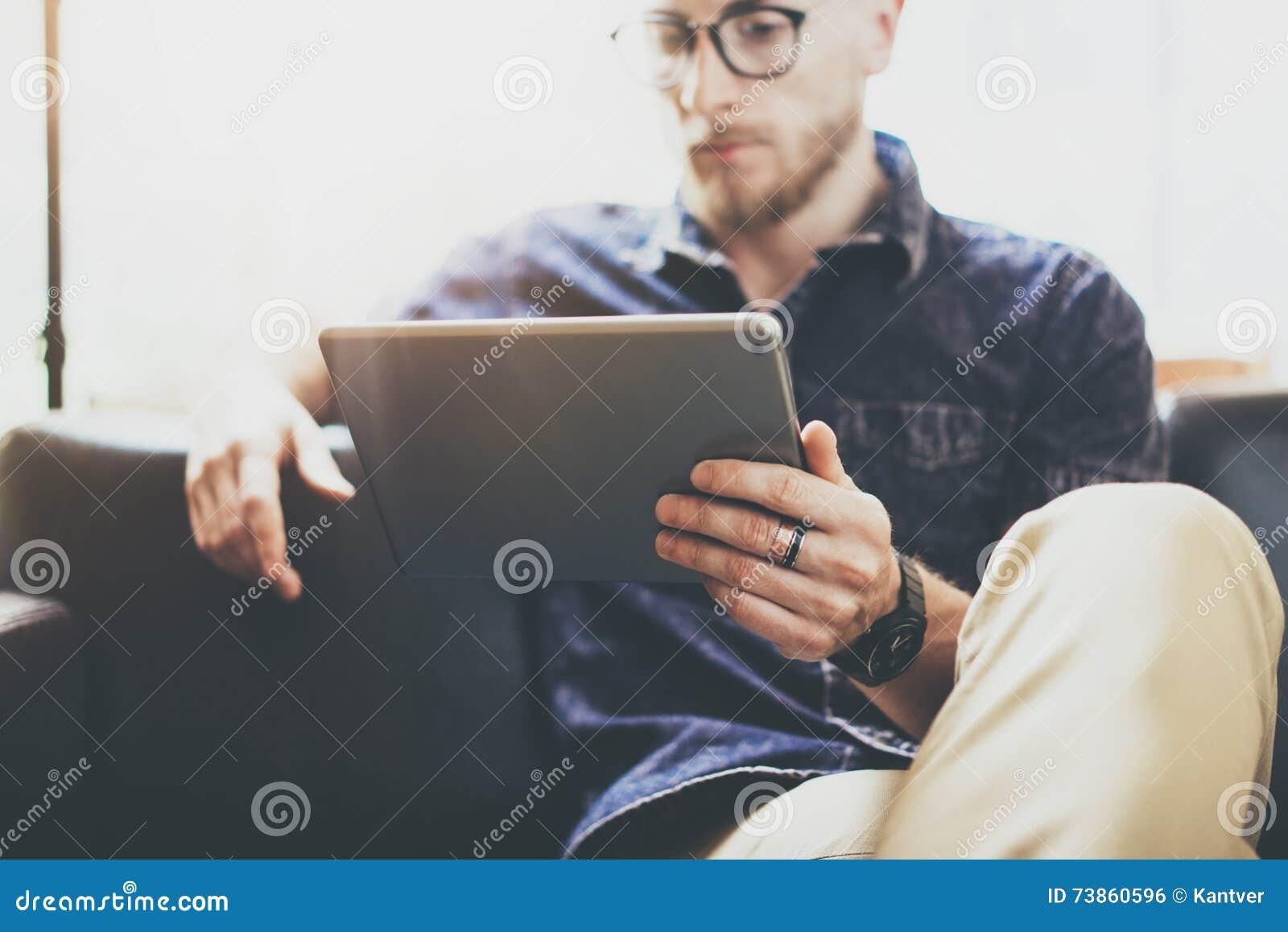 Бородатый специалист по маркетинга работая офис просторной квартиры дизайна интерьера цифровой таблетки современный Человек ослаб