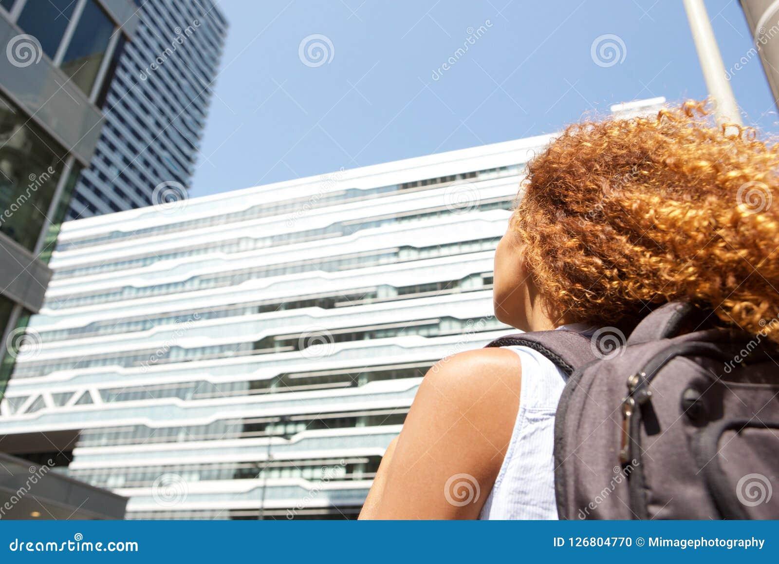 Бортовая молодая женщина портрета с сумкой идя и смотря вверх на зданиях