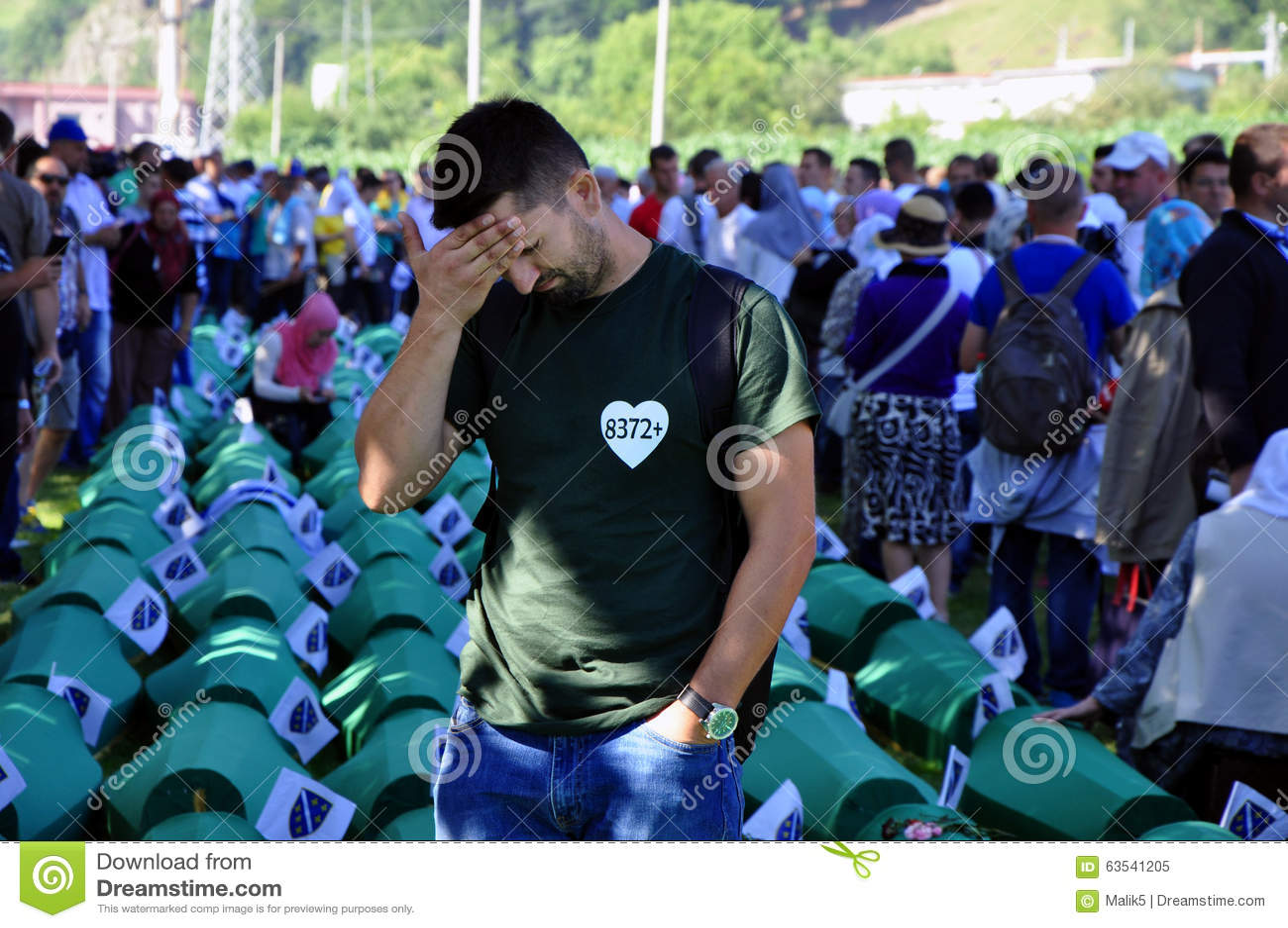 Боснийский мусульманский человек сидит и плачет около гроба его родственника на мемориальном центре в Potocari