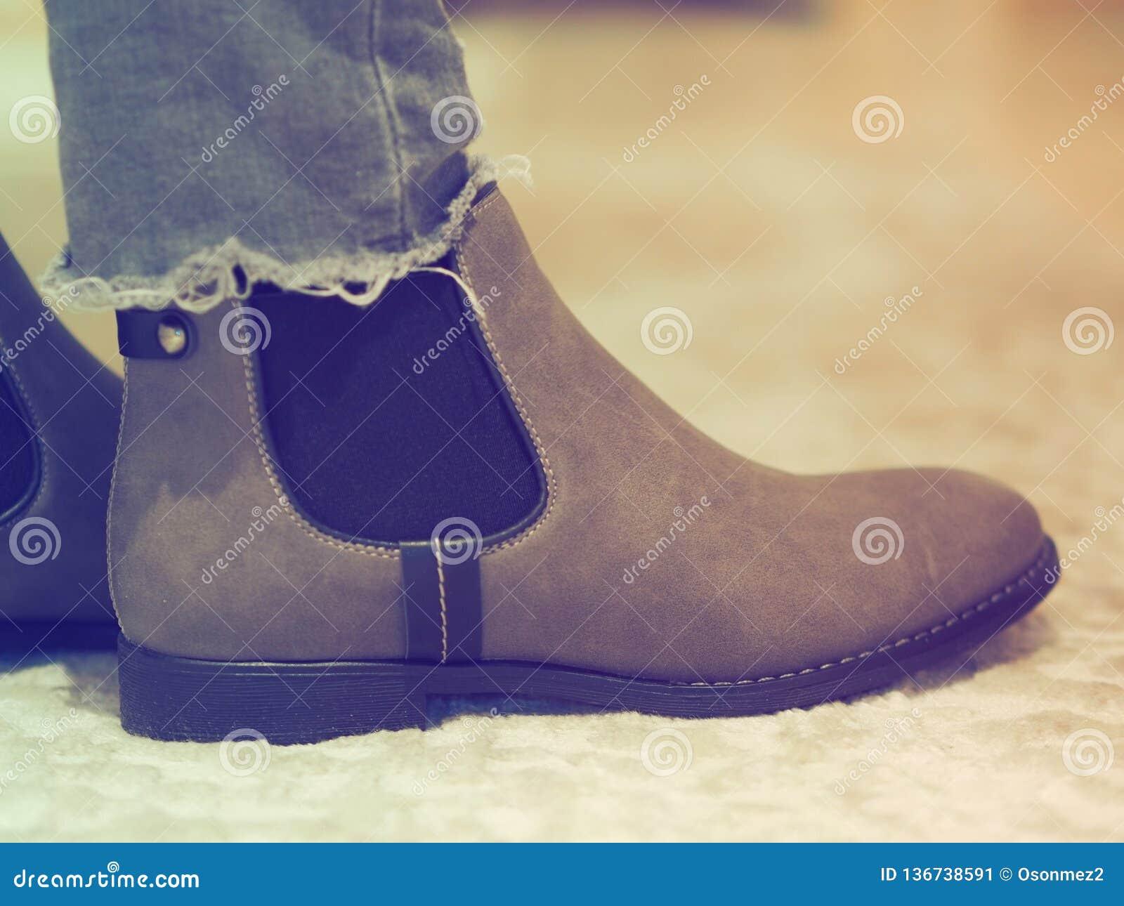 Ботинки зимы женщин Брауна и брюки джинсов