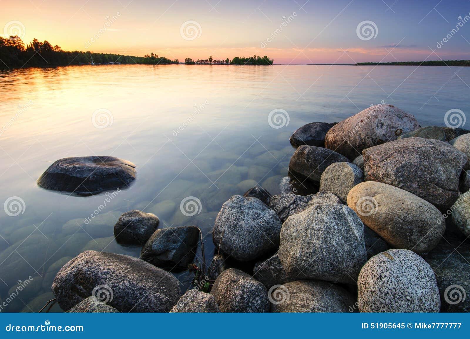 Большие валуны на береге озера на заходе солнца Минесота, США