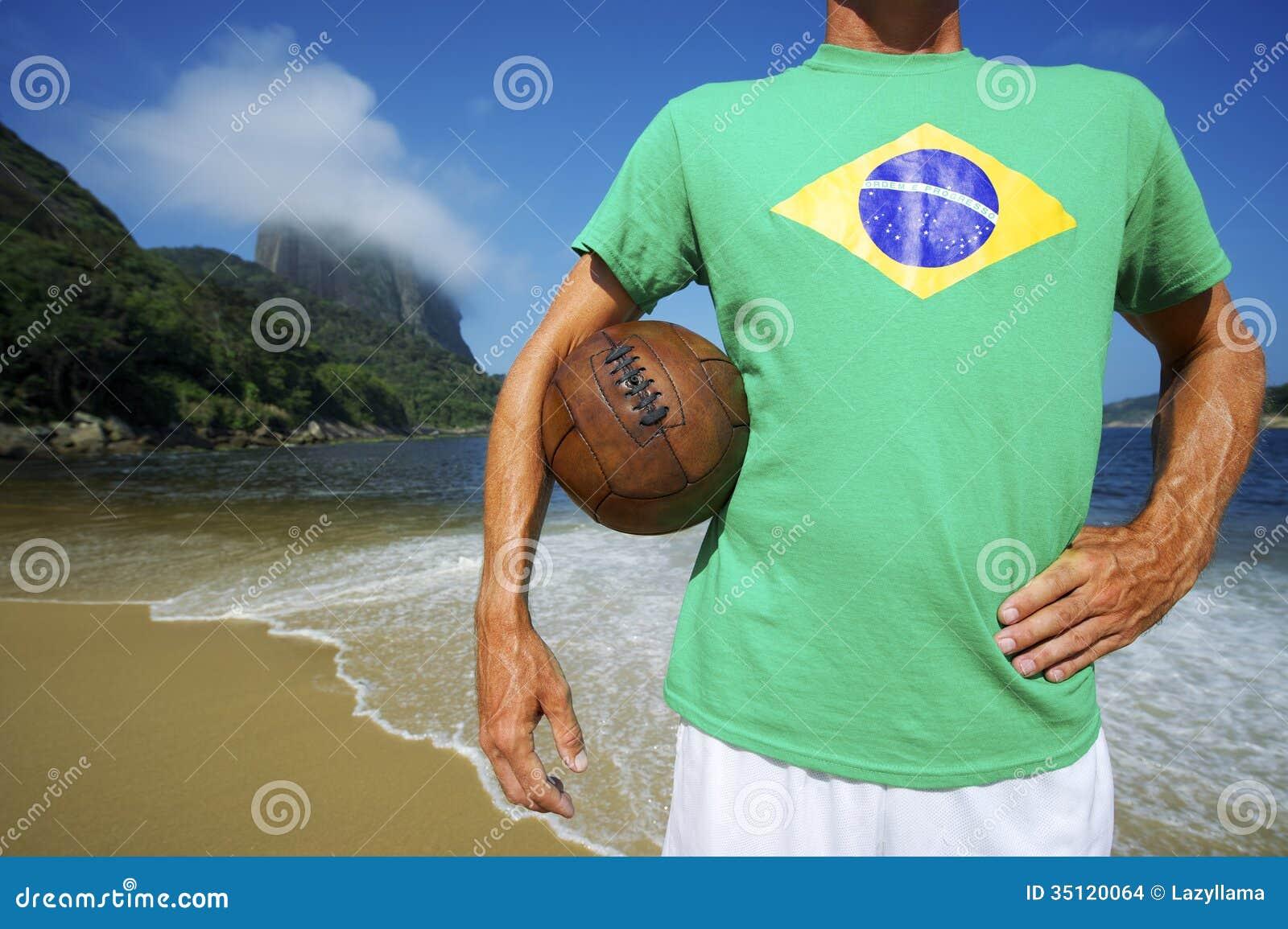 Бразильский футболист футбола стоит на пляже Рио
