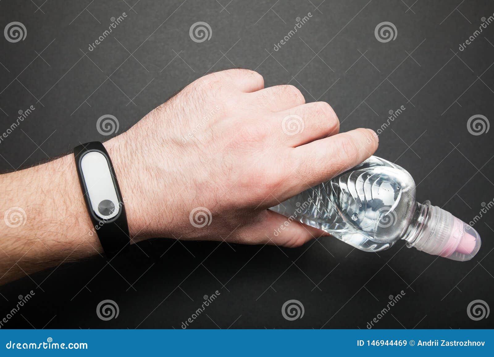 Браслет фитнеса на руке человека с бутылкой воды