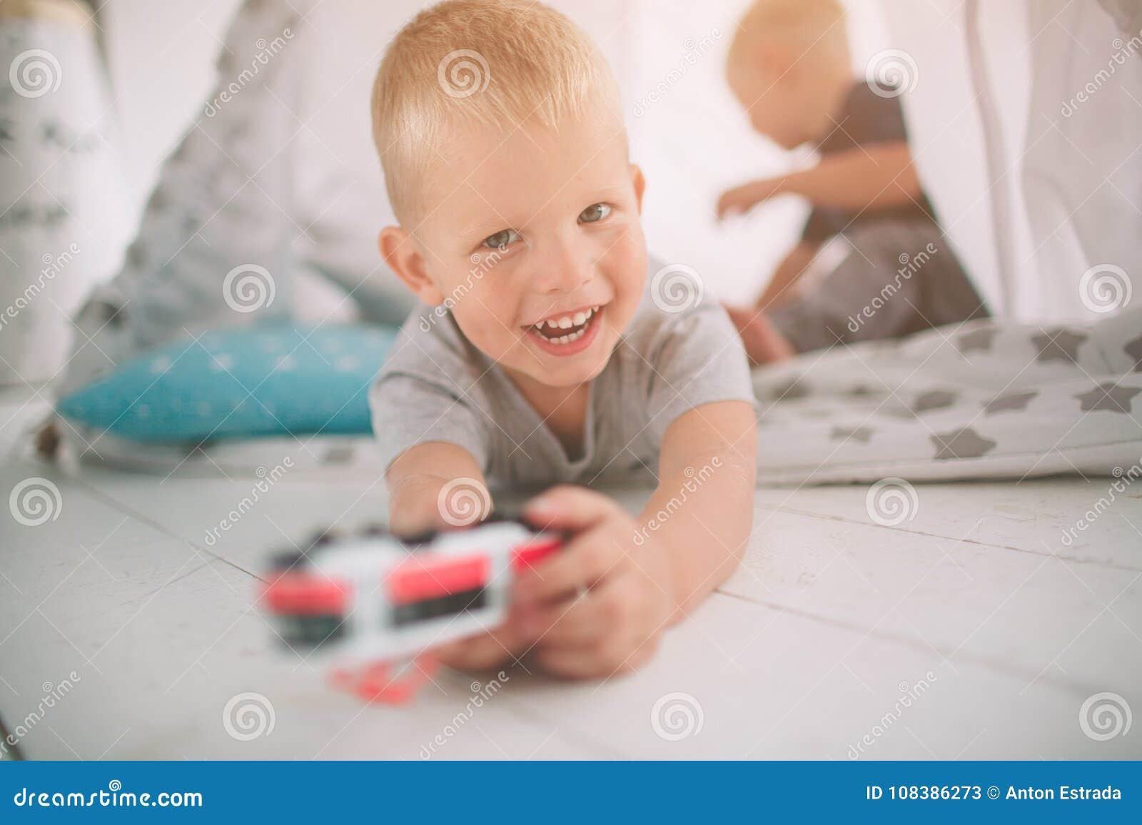 Братья детей кладут на пол Мальчики играют в доме с автомобилями игрушки дома в утре вскользь уклад жизни