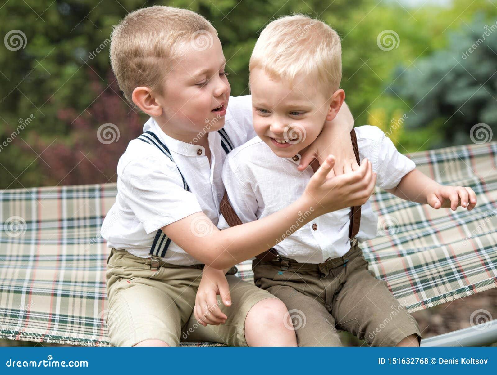 2 брать отдыхают, говорящ секреты в его ухе Мальчики едут в гамаке