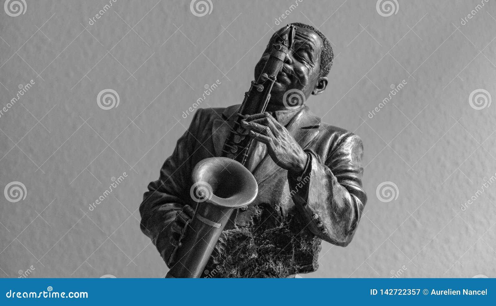 Бронзовая статуэтка человека который играет саксофон