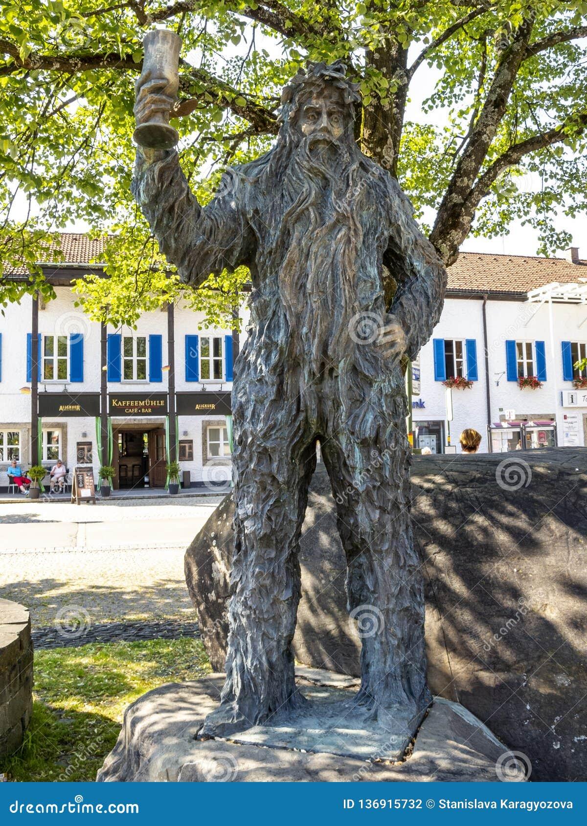 Бронзовая статуя Wilde-Maendle или статуя дикого человека на солнечный летний день в Оберстдорфе, Германии