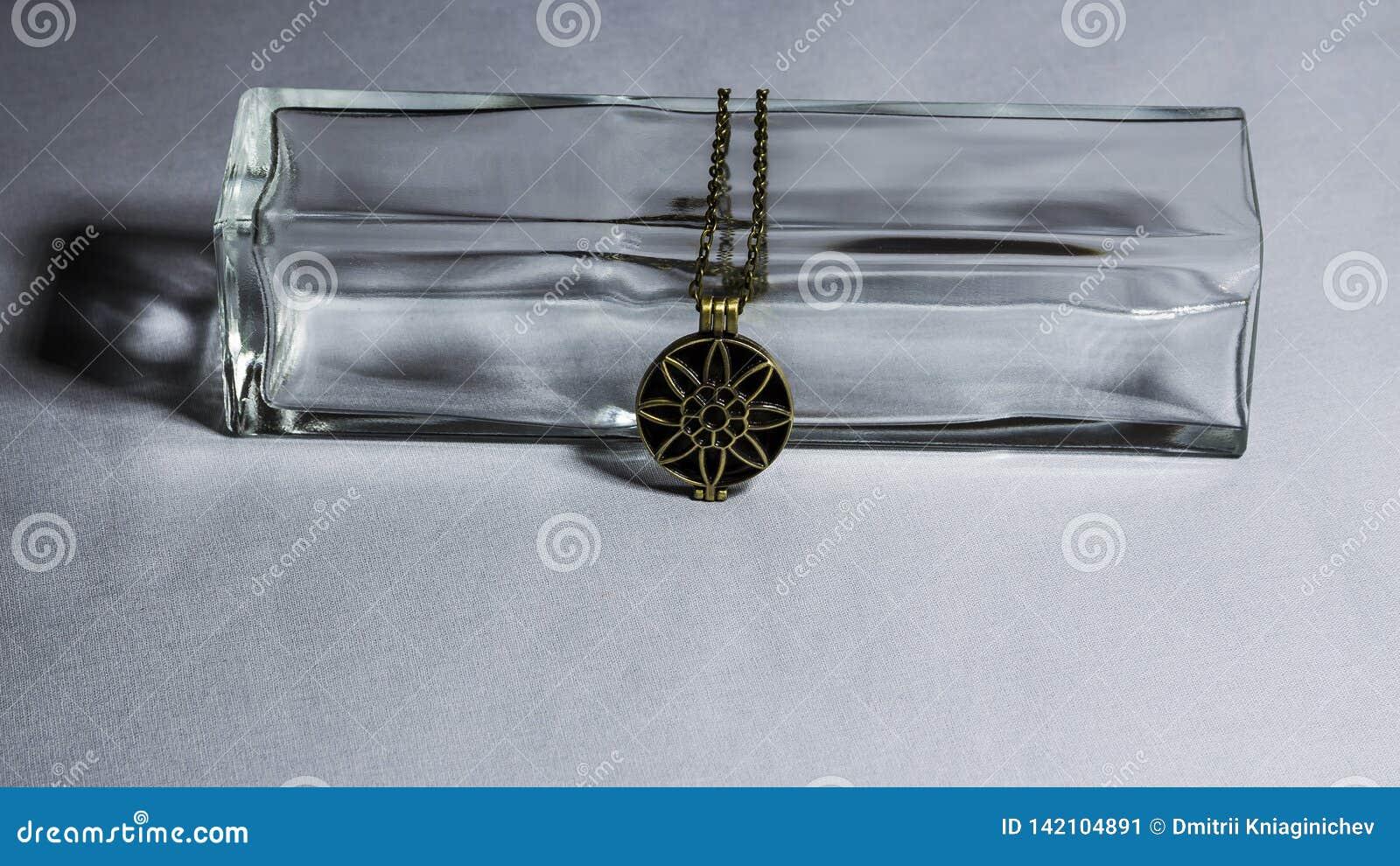 Бронзовый шкентель на предпосылке стеклянной вазы