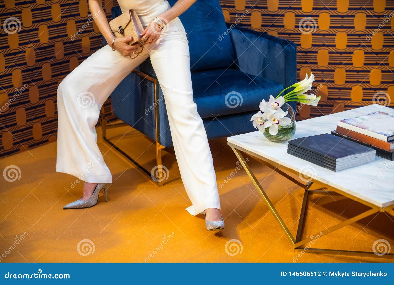 Брюки модели высокой моды нося белые и серебряные высокие пятки держа сумку с ювелирными изделиями