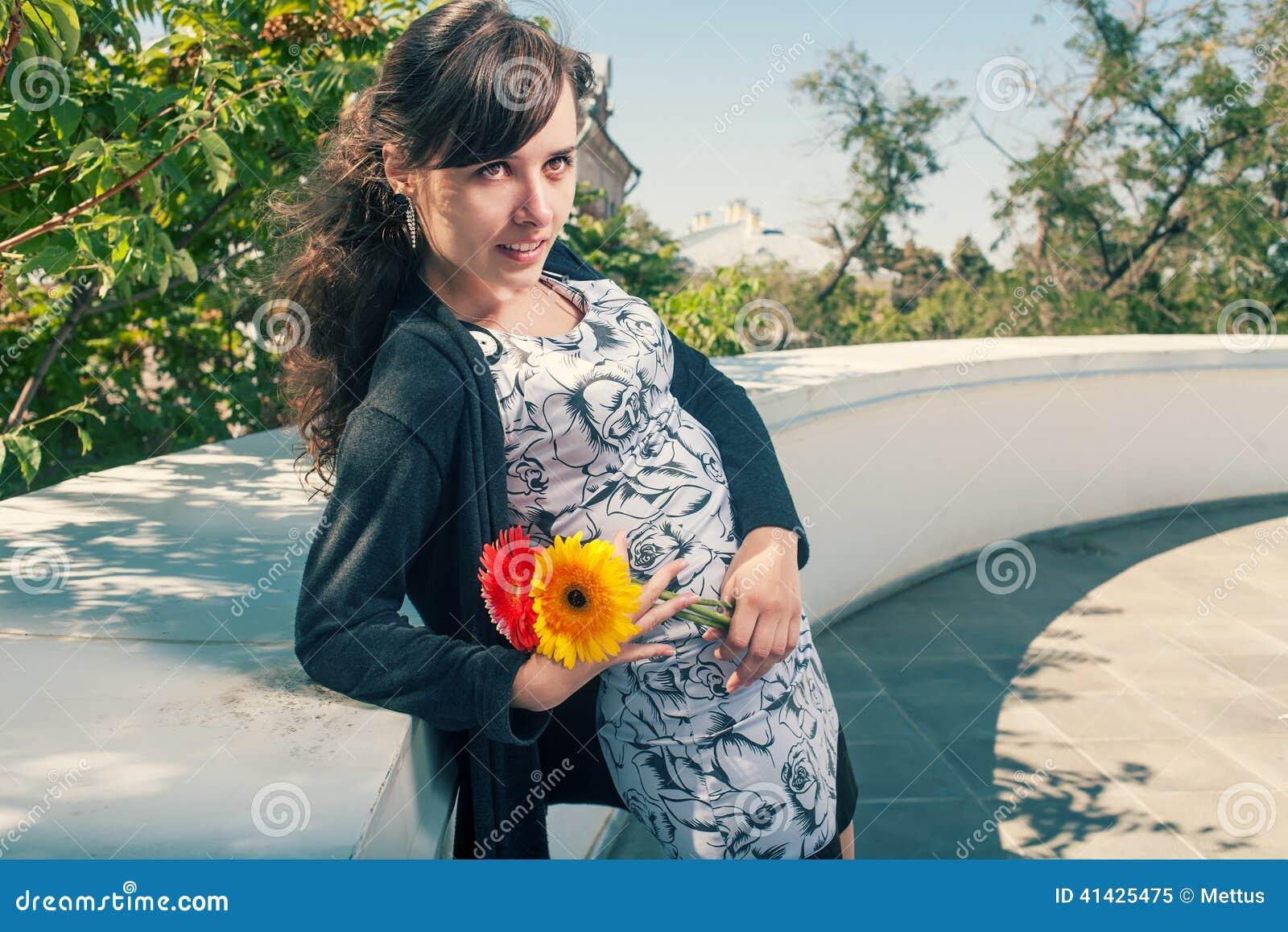 Брюнет в платье постном против стены с пуком цветков в h