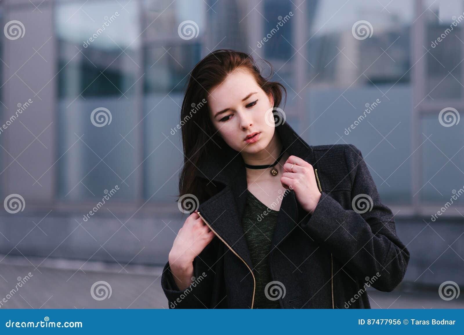 Брюнет женщины стильного внешнего портрета красивое одело в черноте и предпосылке серого цвета города предпосылки