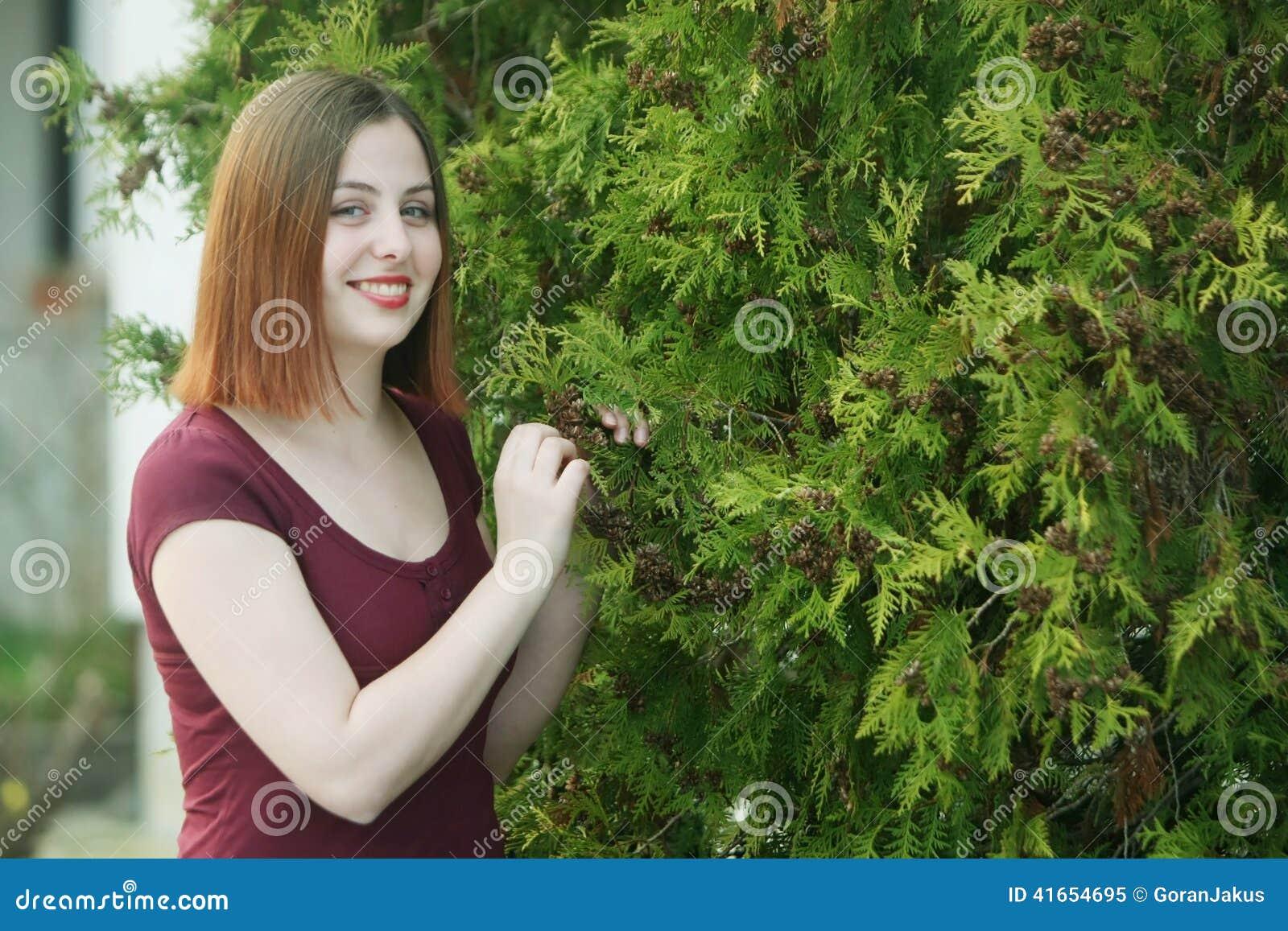 Брюнет представляя с деревьями
